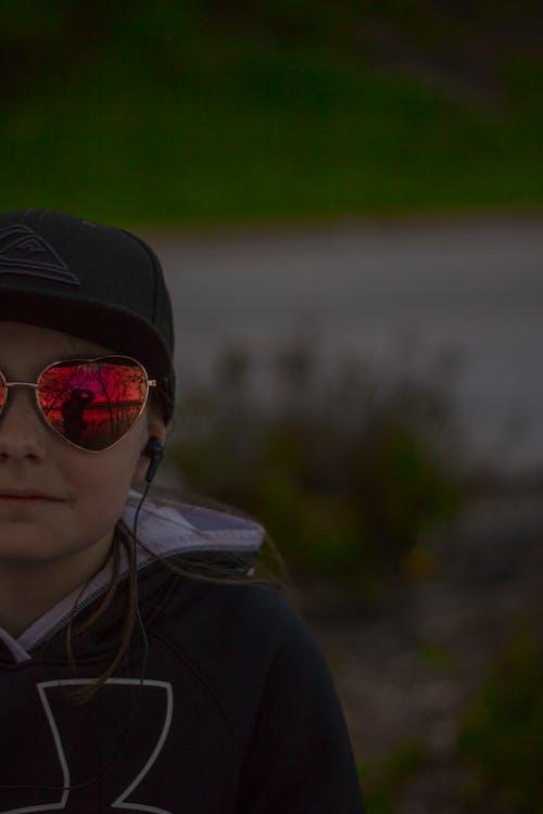 Standing Woman Wearing Black Hoodie and Sunglasses