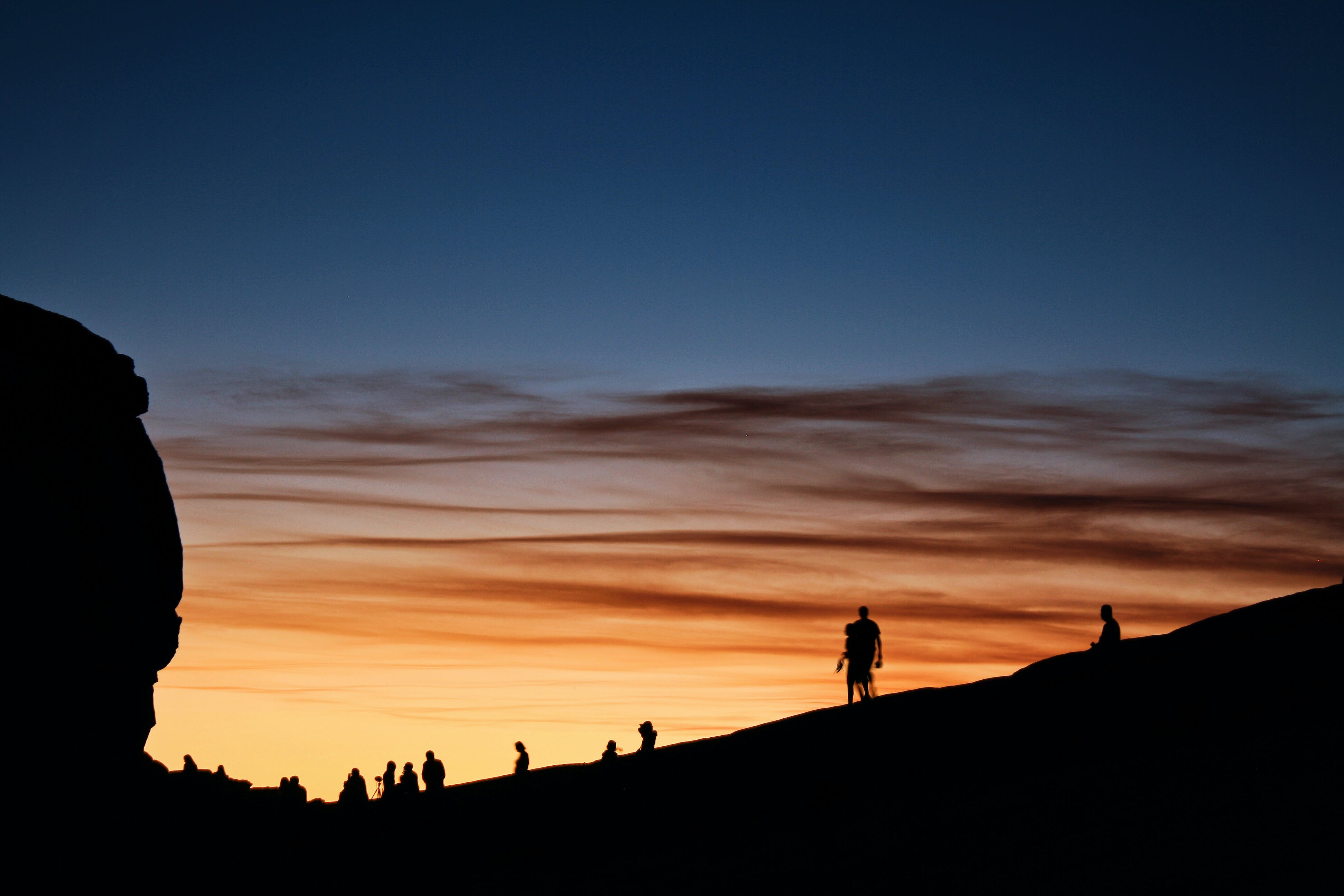 Silhouette of People Walking on Mountain during Golden Hour