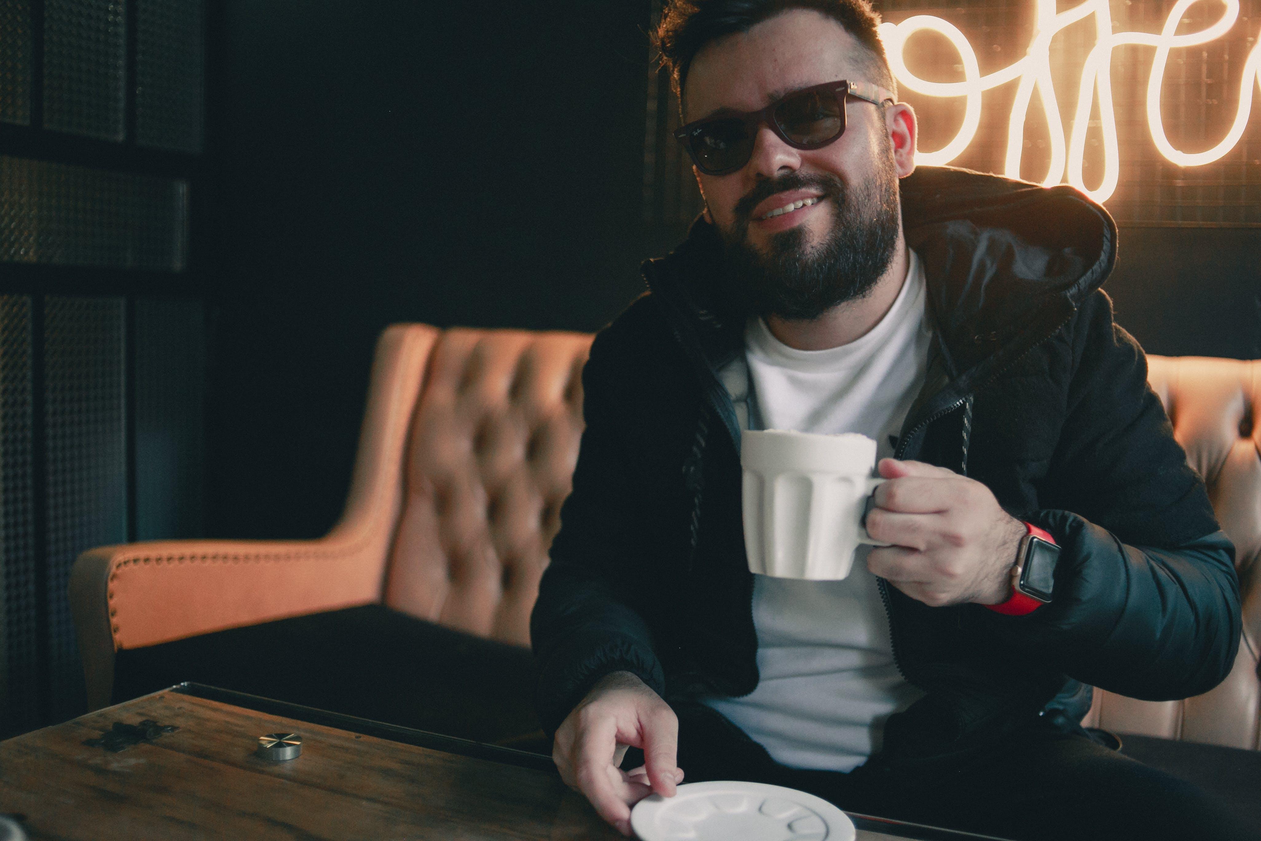 Smiling Man Sitting Near Table Holding Ceramic Mug Inside Room