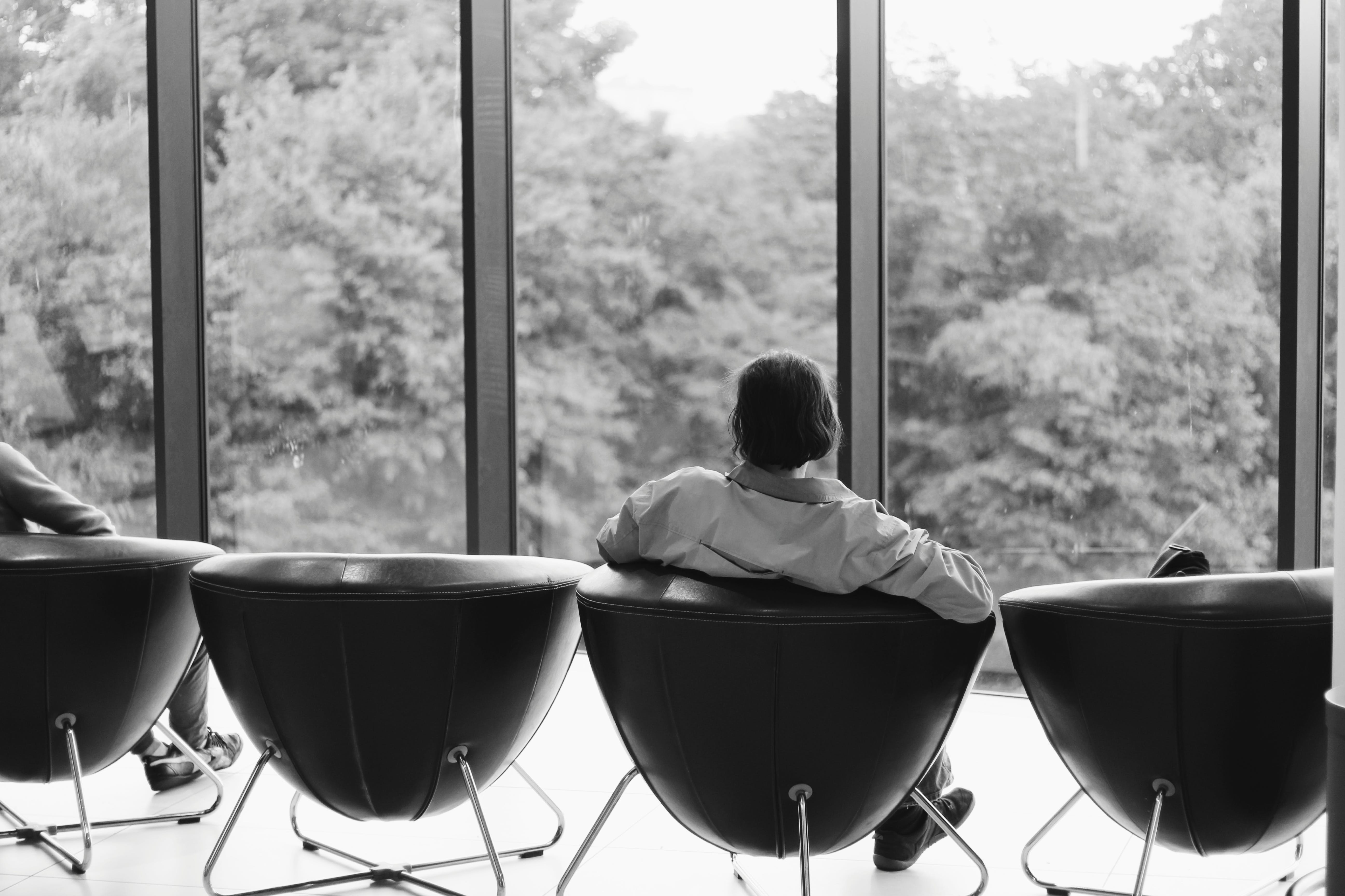 Grayscale Photo of Person Sitting on Leather Chair Looking in Front of Clear Glass Door