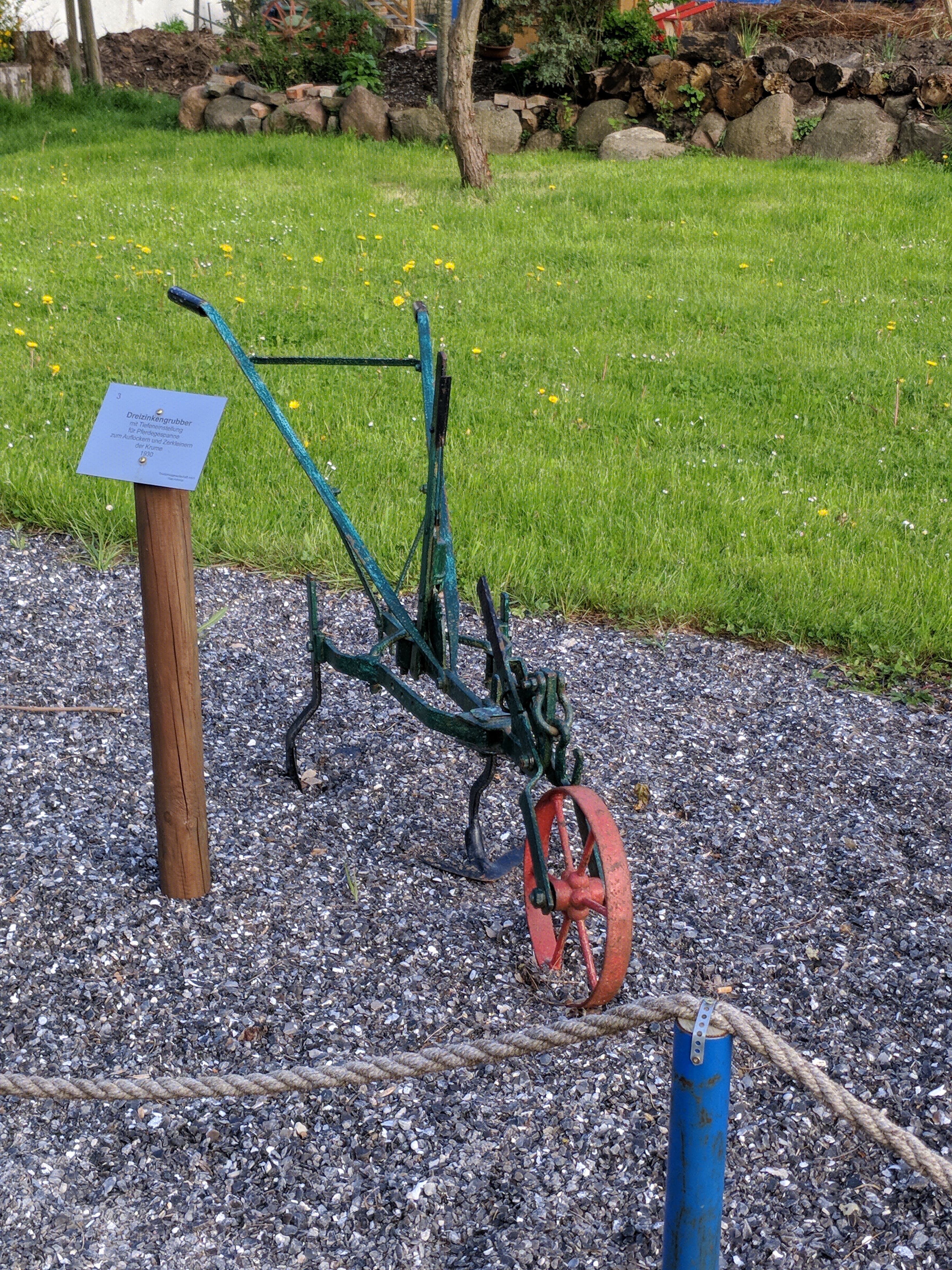 Green and Red Wheelbarrow Frame Near Green Grass