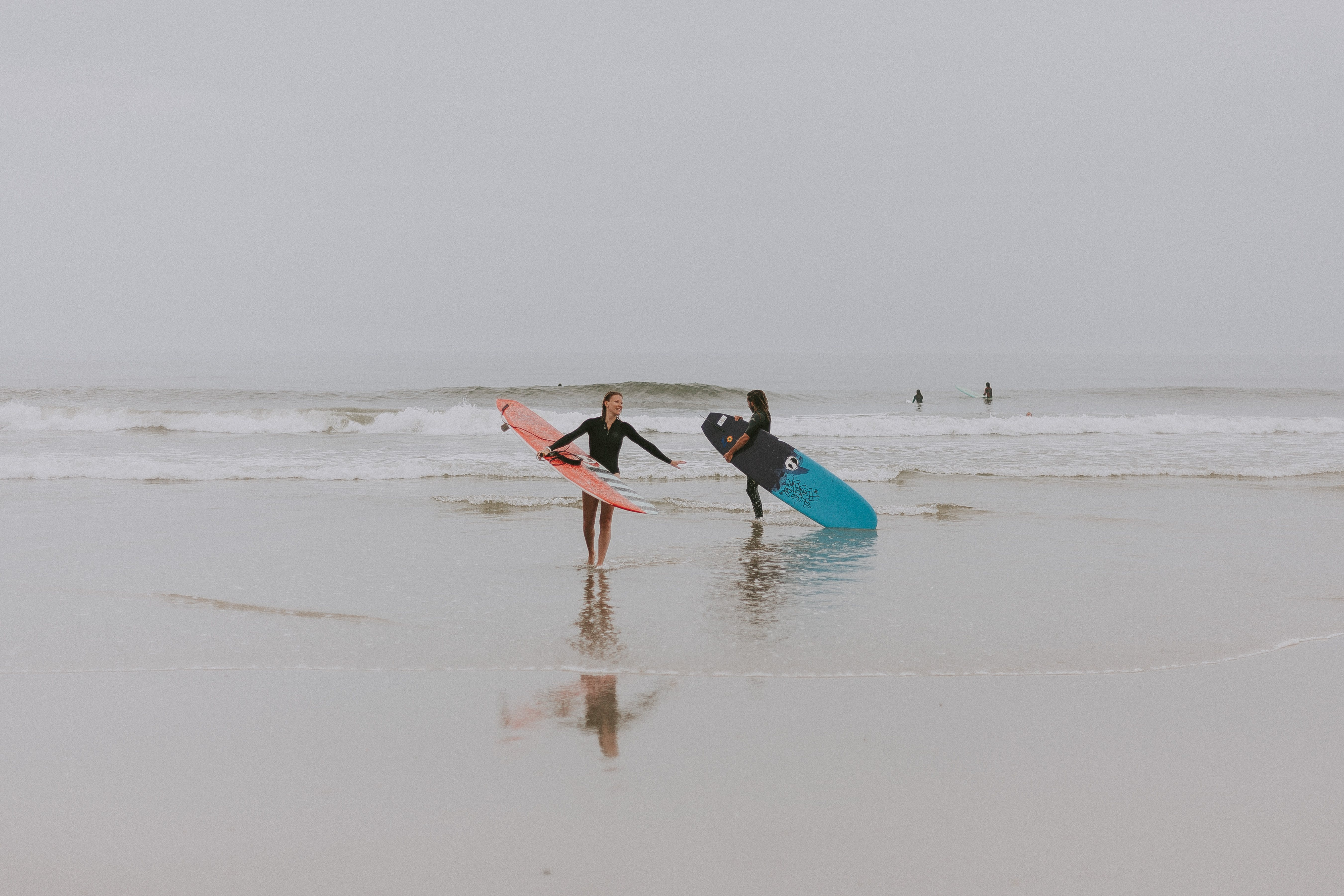 Photography of People On Seashore Holding Surboard