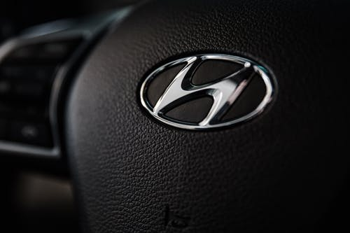 Shallow Focus Photography of Hyundai Emblem