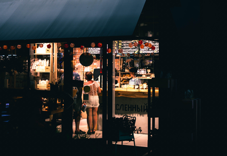 Woman in White Top Mini Dress Standing Near Store Door
