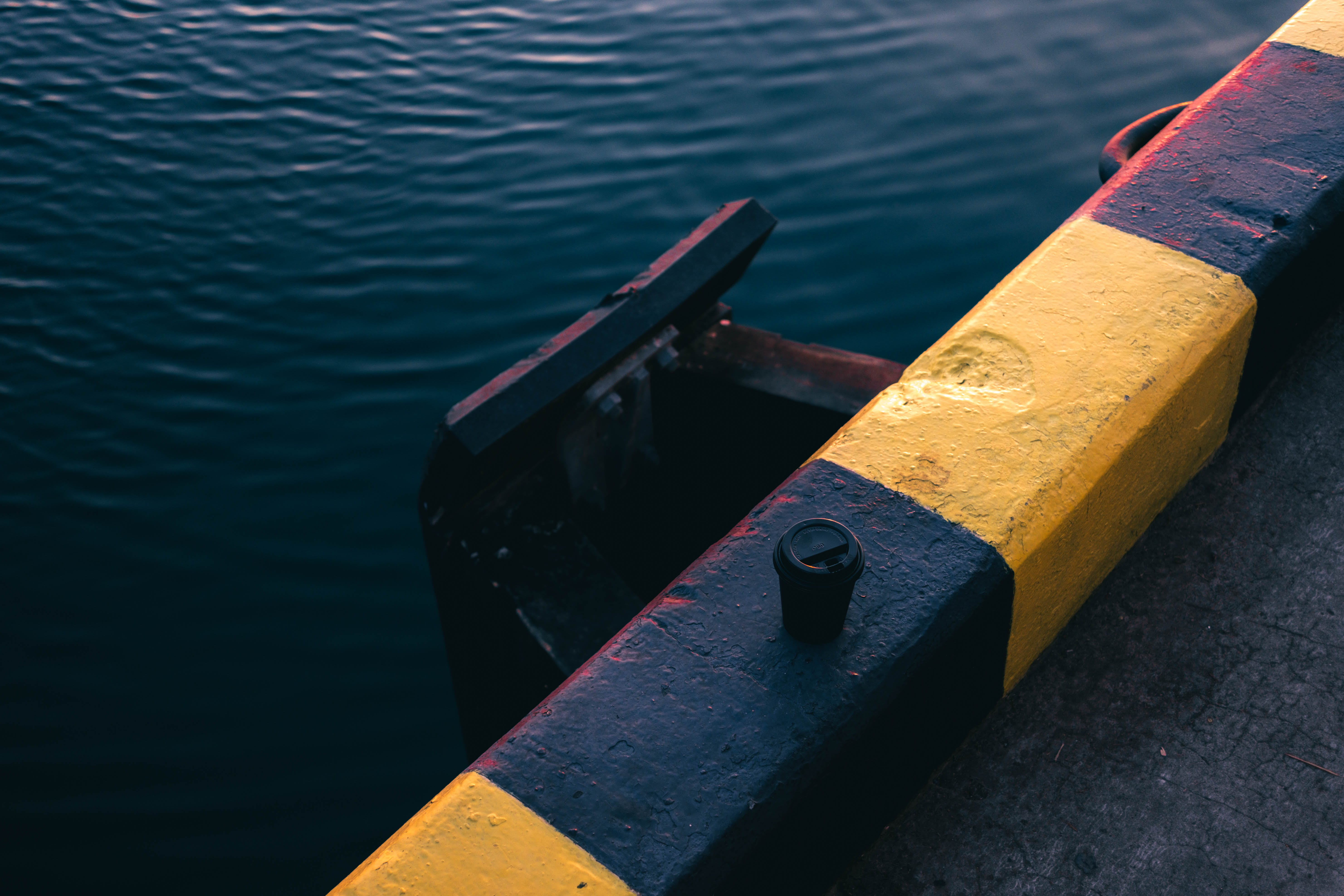 Yellow and Black Painted Bar Near Body of Water