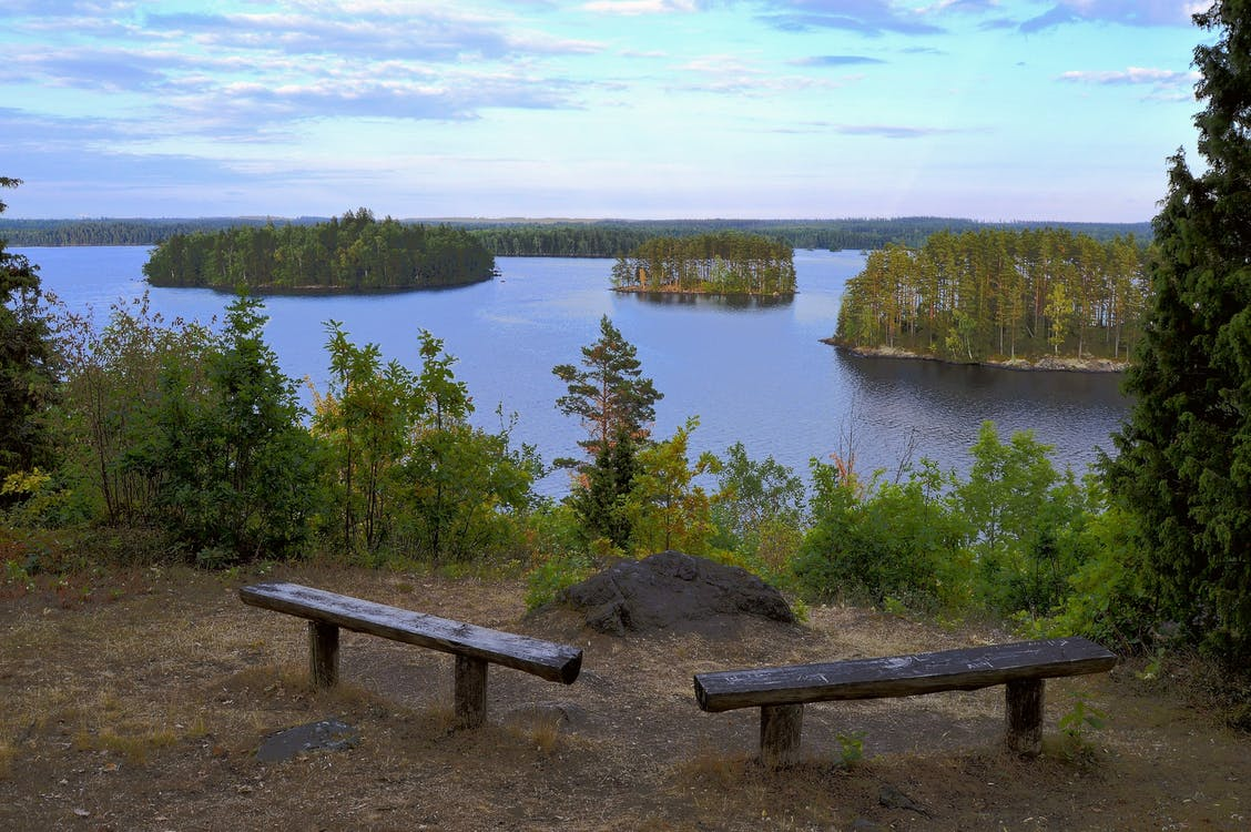 Benches Overlooking Body Of Water At Daytime
