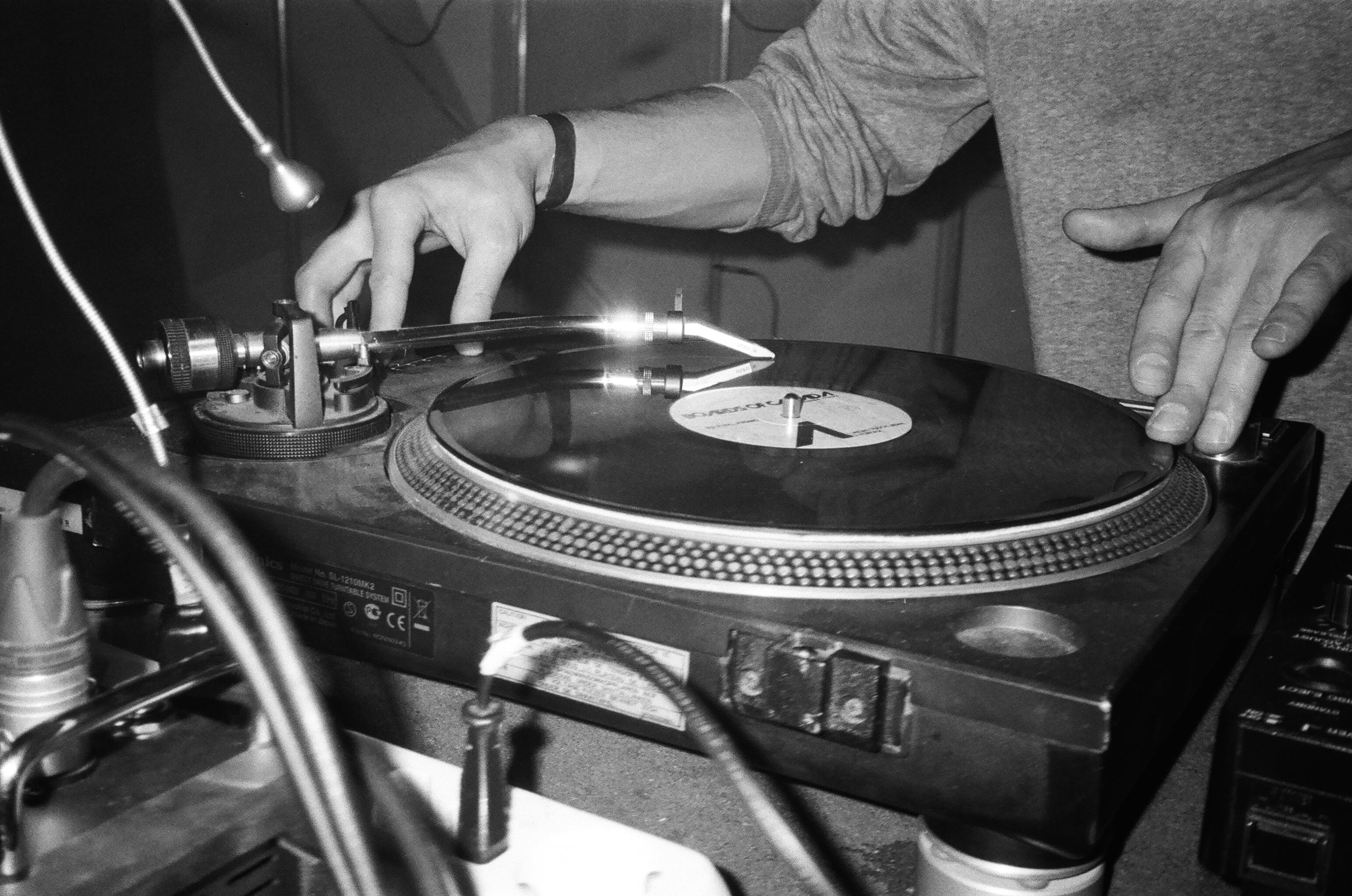 Grayscale Photography of Person Playing Turntable