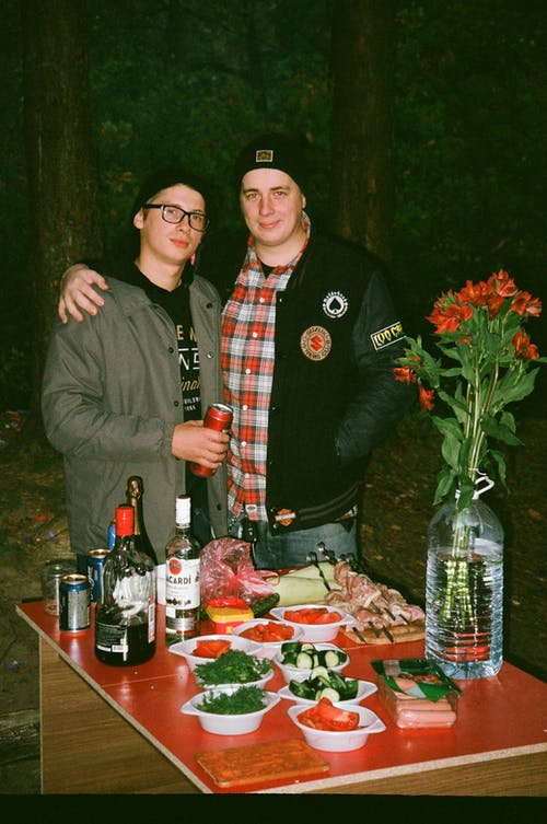 Two Men Standing Beside Each Other at the Back of Table
