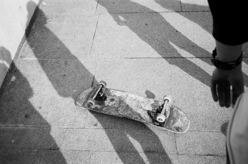 Grayscale Photo of Up-side-down Skateboard