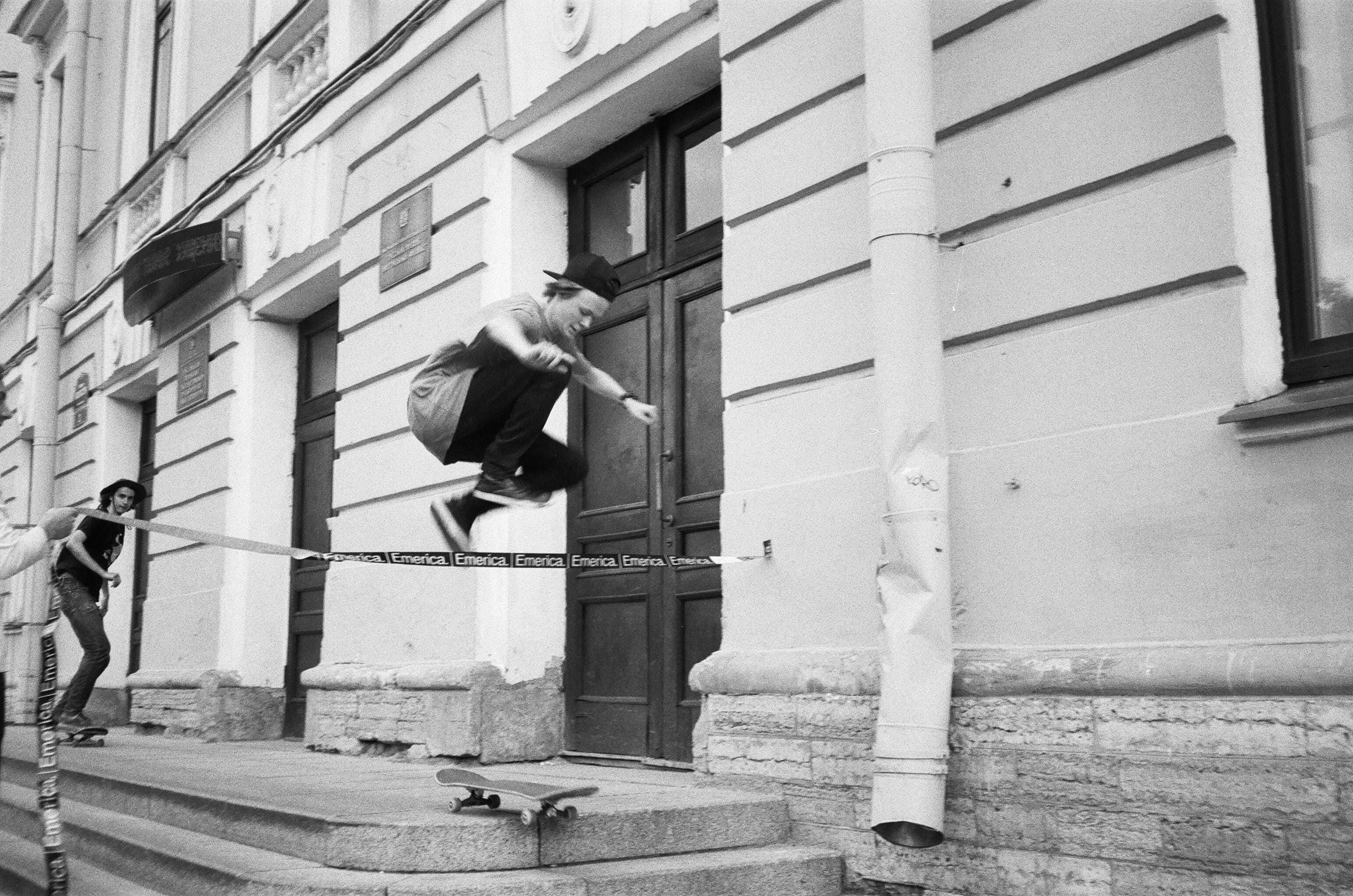Grayscale Photography of Man Riding Skateboard Making Tricks Near Concrete Building