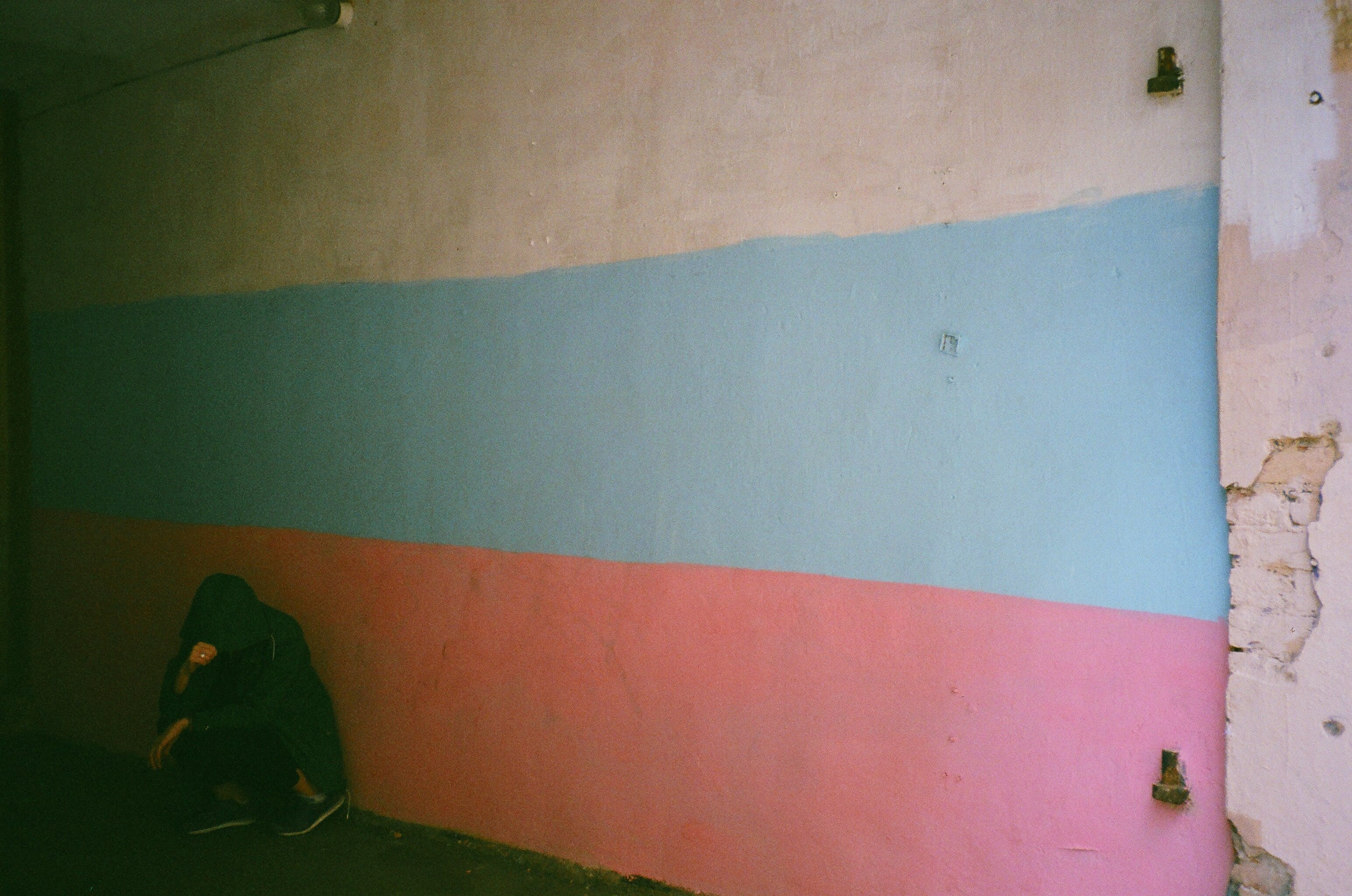 Person Leaning on Blue, White, and Pink Wall