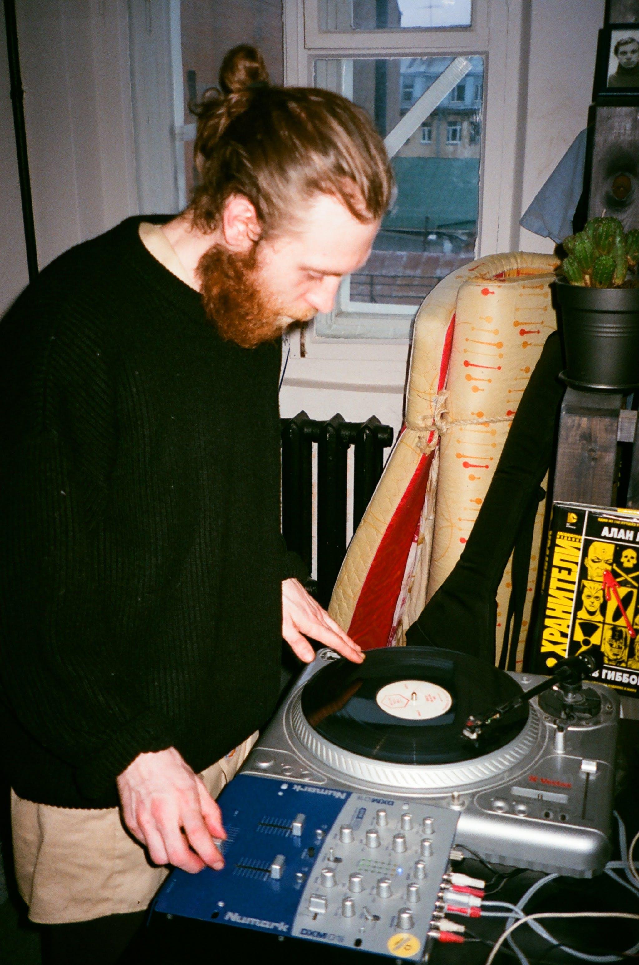Man in Green Sweater Using Dj Controller