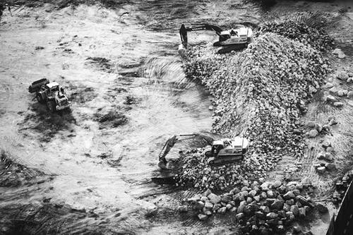 Aerial Photography of Two Excavators on Pile of Stones
