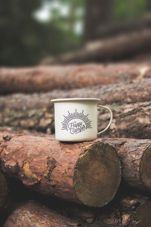White Happy Camper-printed Cup on Brown Wooden Log