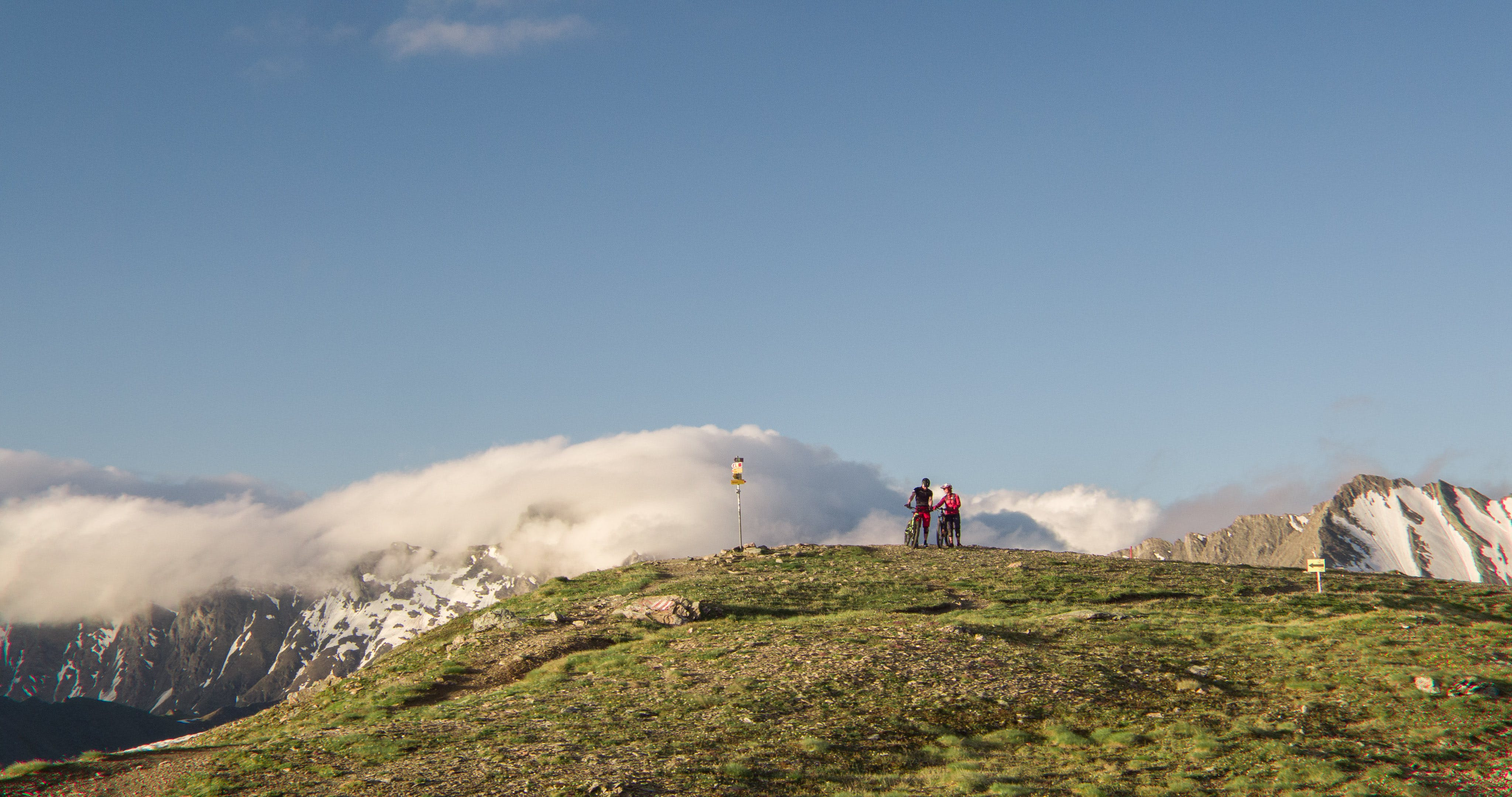Two Man Standing on Mountain Near Mountain Covered by Snows