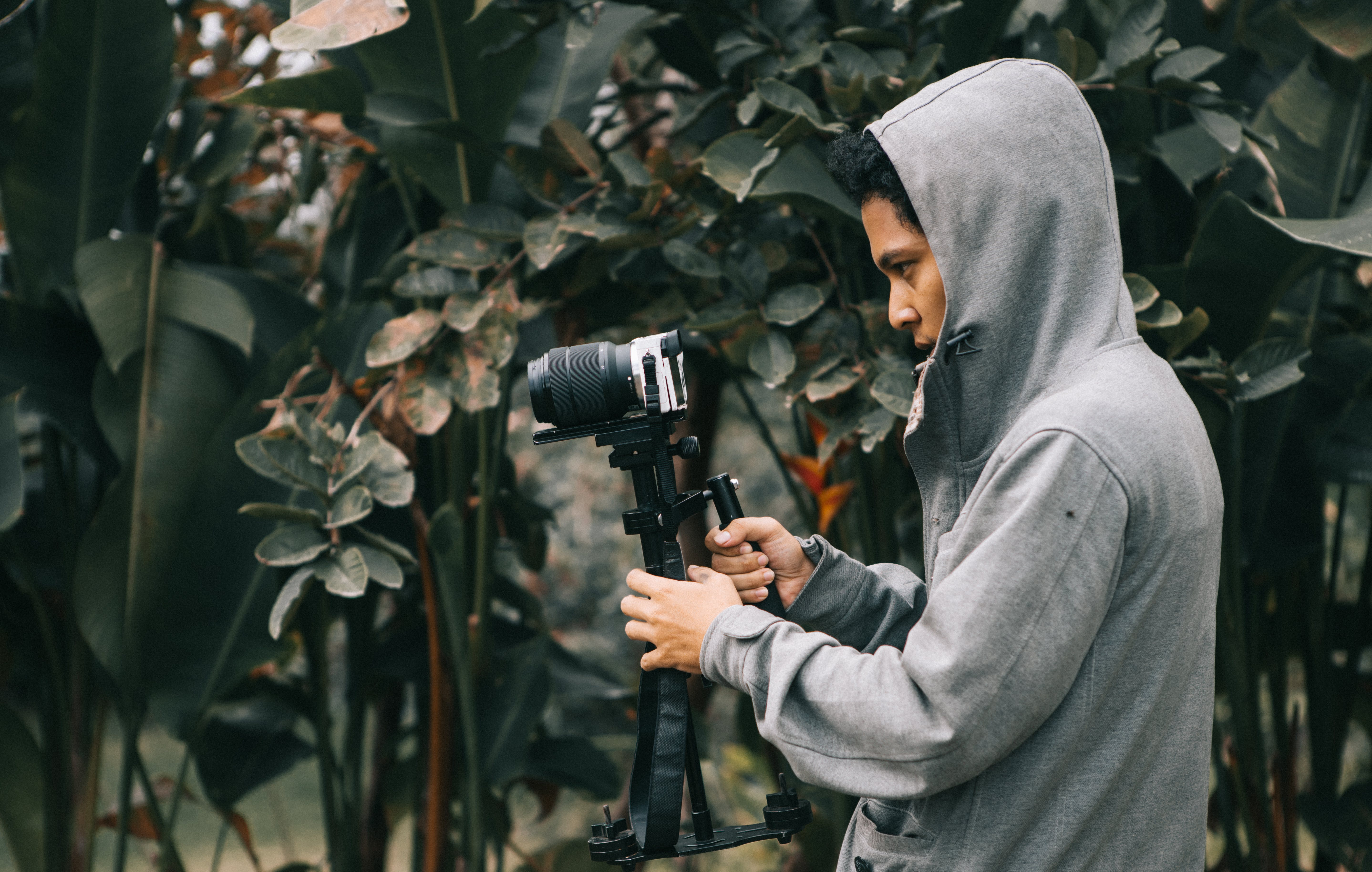 Man in Hooded Jacket Holding Camera With Stablizer