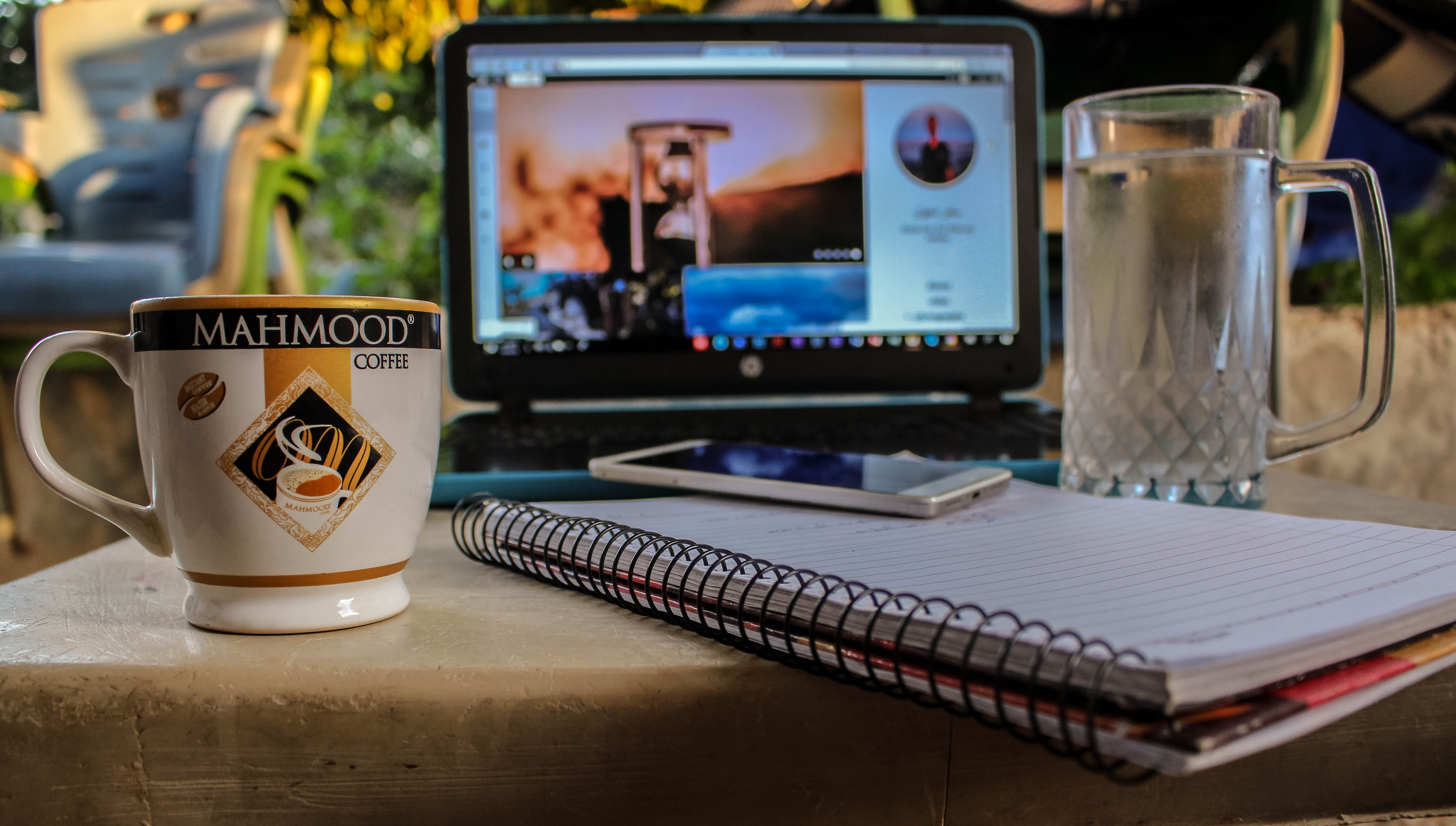 White Smartphone on Spiral Notebook Between Ceramic Mug and Glass Beer Mug Near Black Computer Monitor Showing Hour Glass