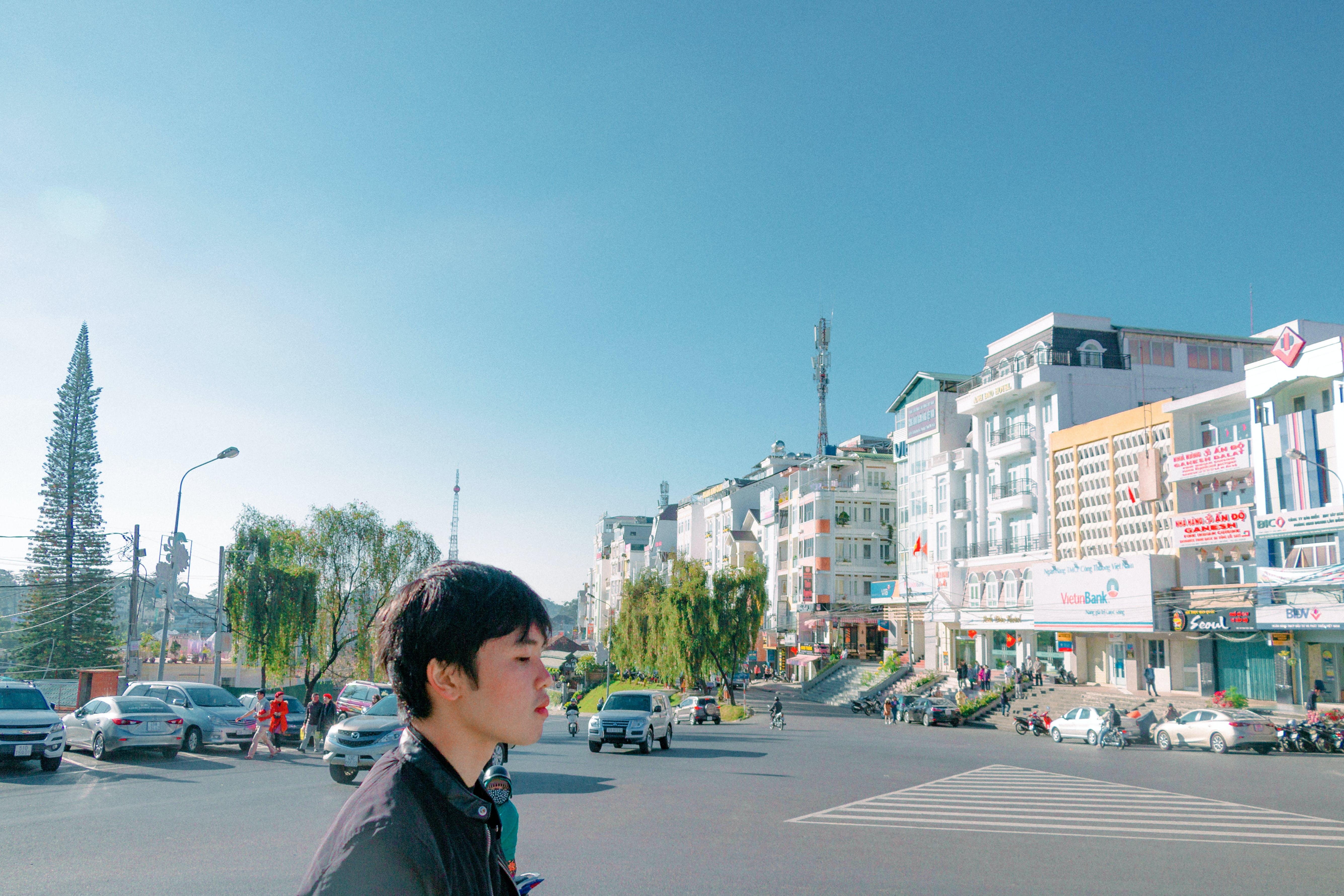 Man Walking on Street Overlooking Building Under Blue Sky