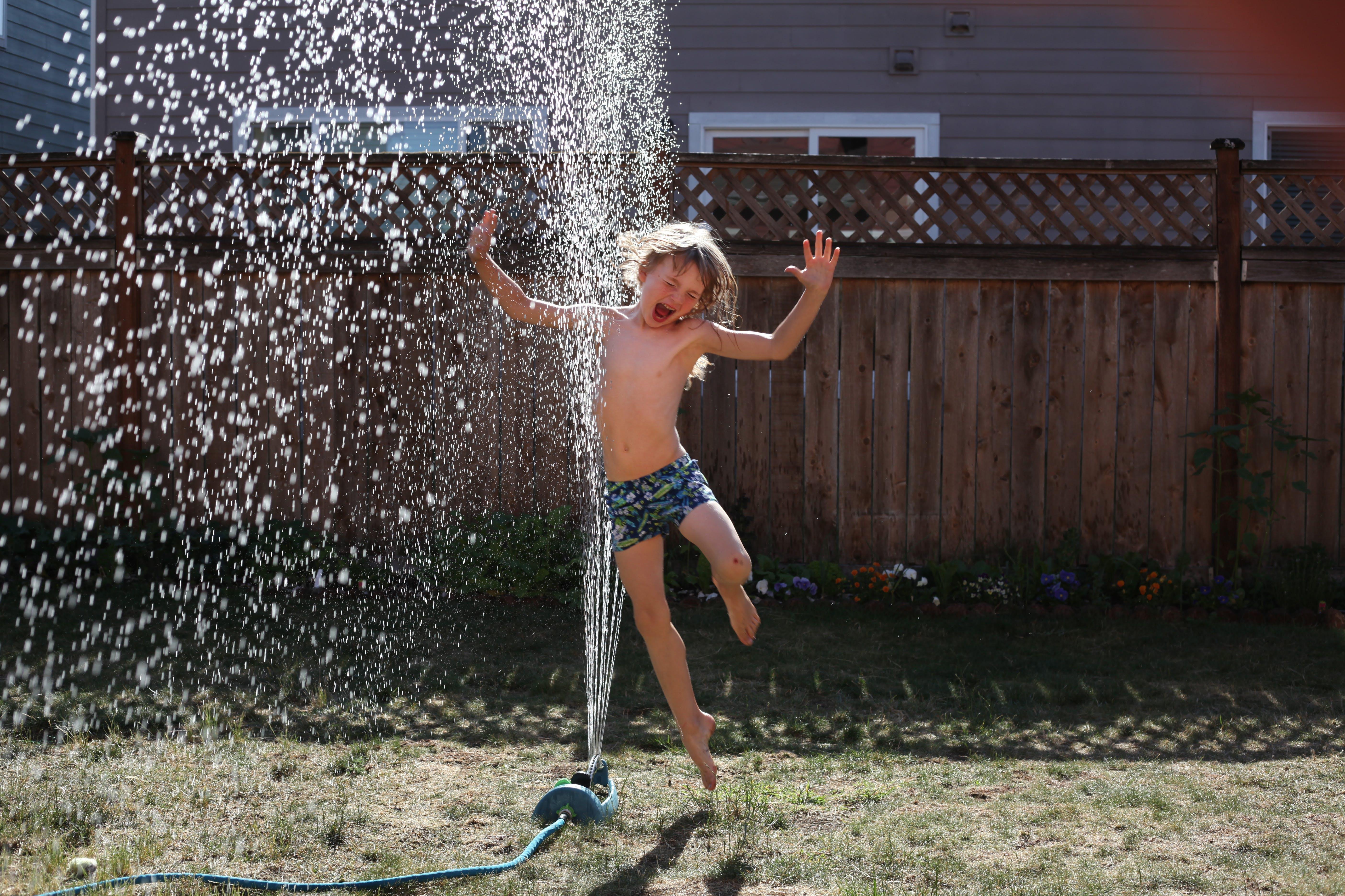 Boy Jumping Near Sprinkler