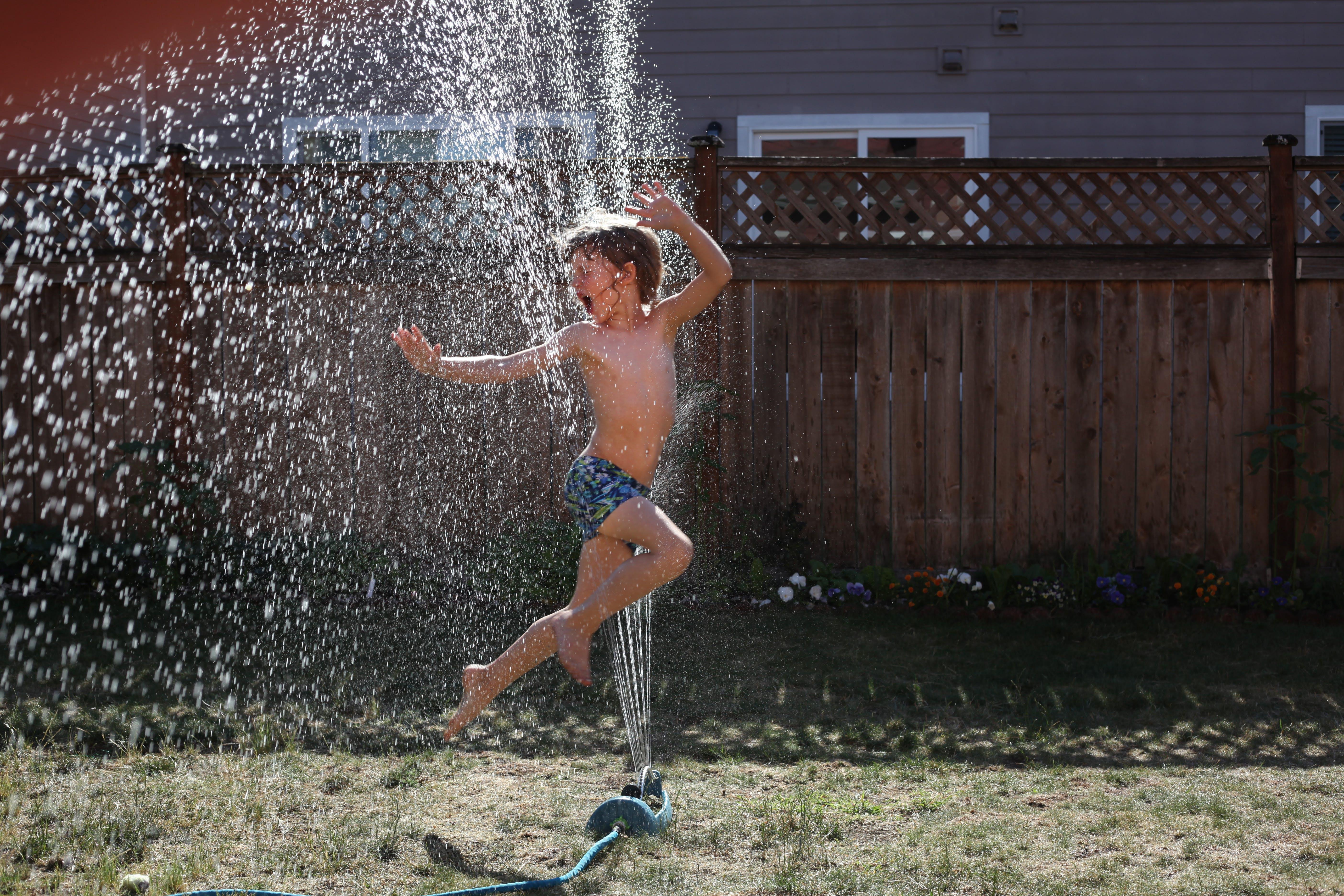 Boy Jumping on Water Sprinkler