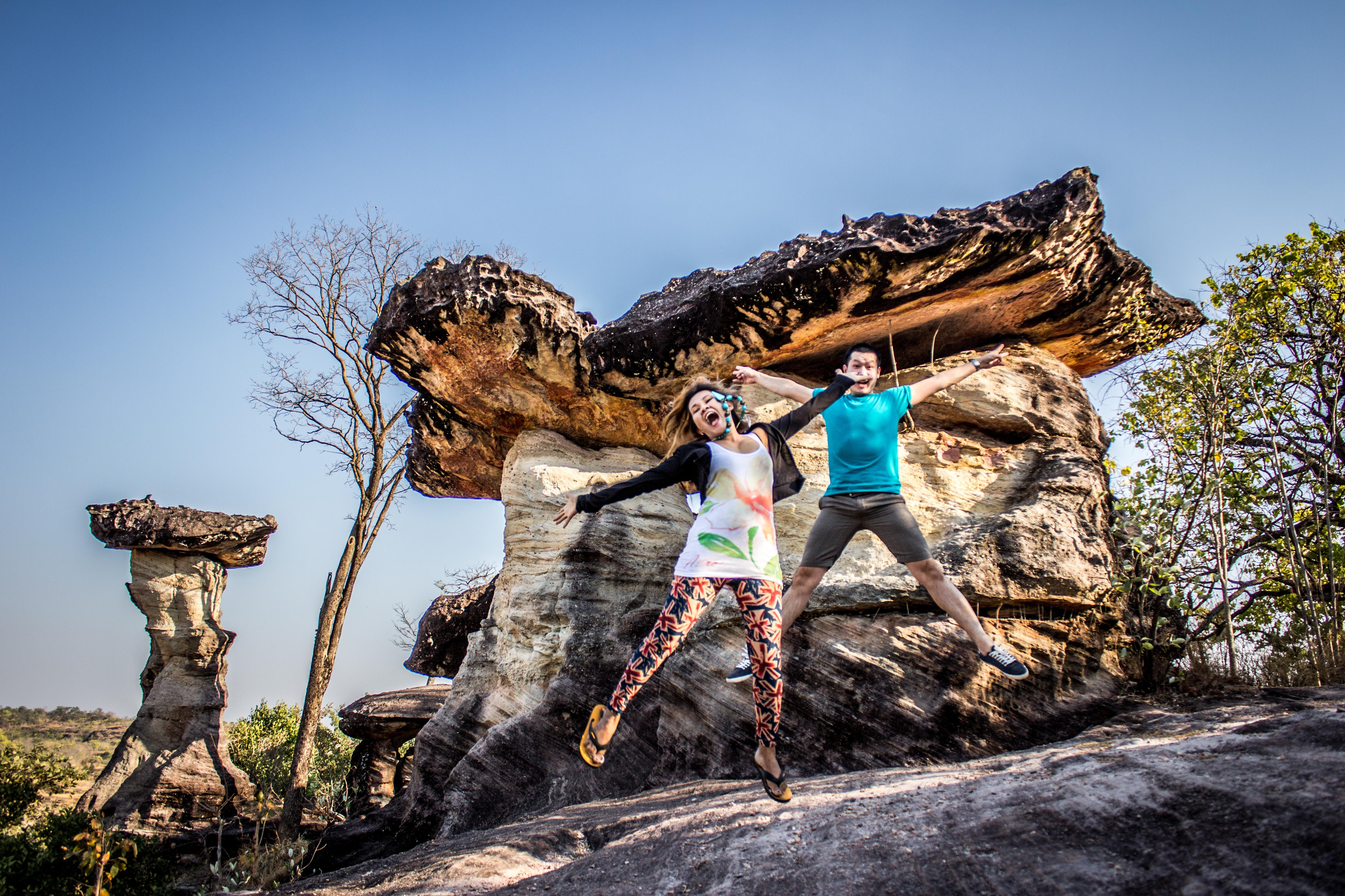 Man and Woman Jumping on Rocky Cliff