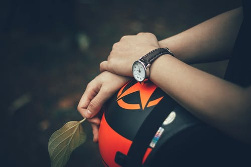 Person Holding Black and Orange Helmet
