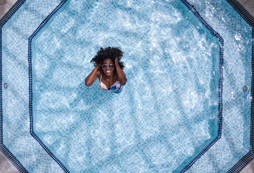 Aerial Photo of Woman Wearing White and Blue Bikini Top Standing on Swimming Pool
