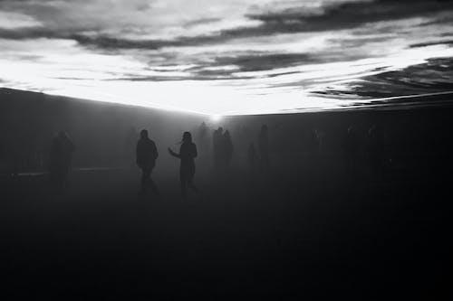 Personnes Debout Sur Une Surface Noire à L'aube