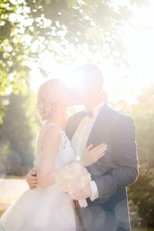 Bride And Groom Kissing Near Tree Against The Sun Photo
