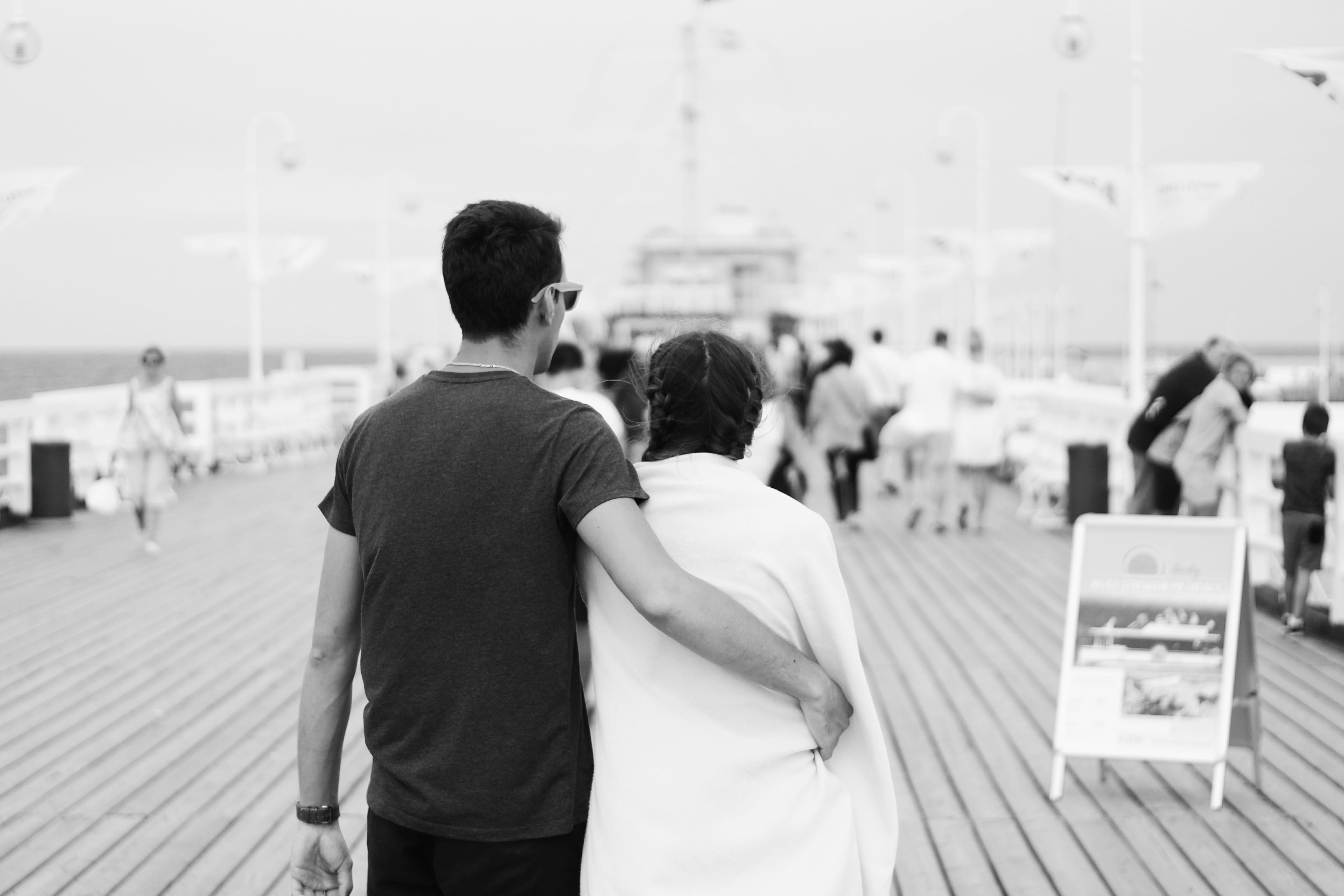 Monochrome Photography of Couple on Boardwalk