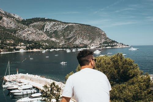 Man Wearing White Shirt and Sunglasses in Front of Boats and Mountain While Looking Right Side Under Blue Sky