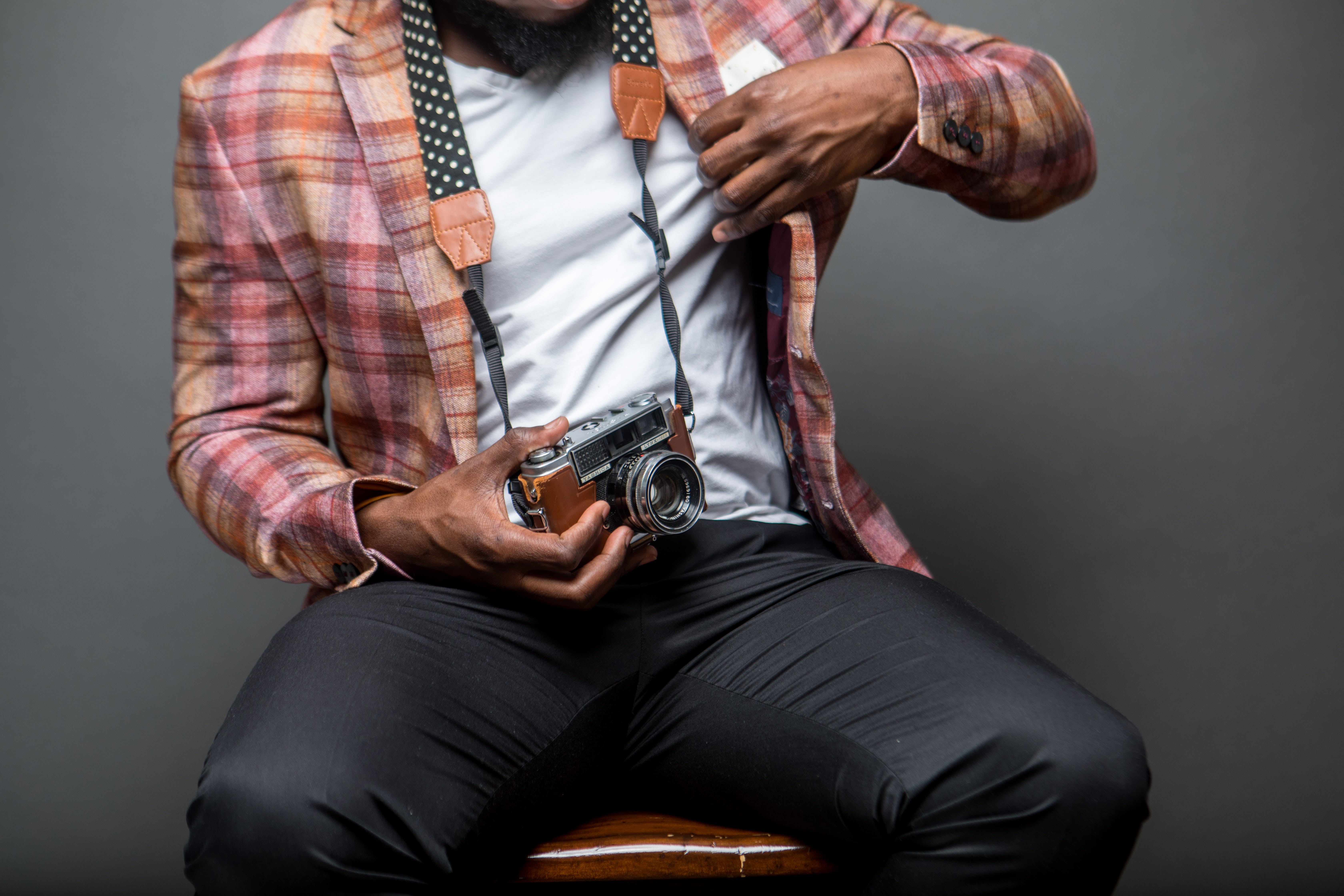 Man Wearing Button-up Shirt Holding Black and Brown Camera While Sitting on Chair