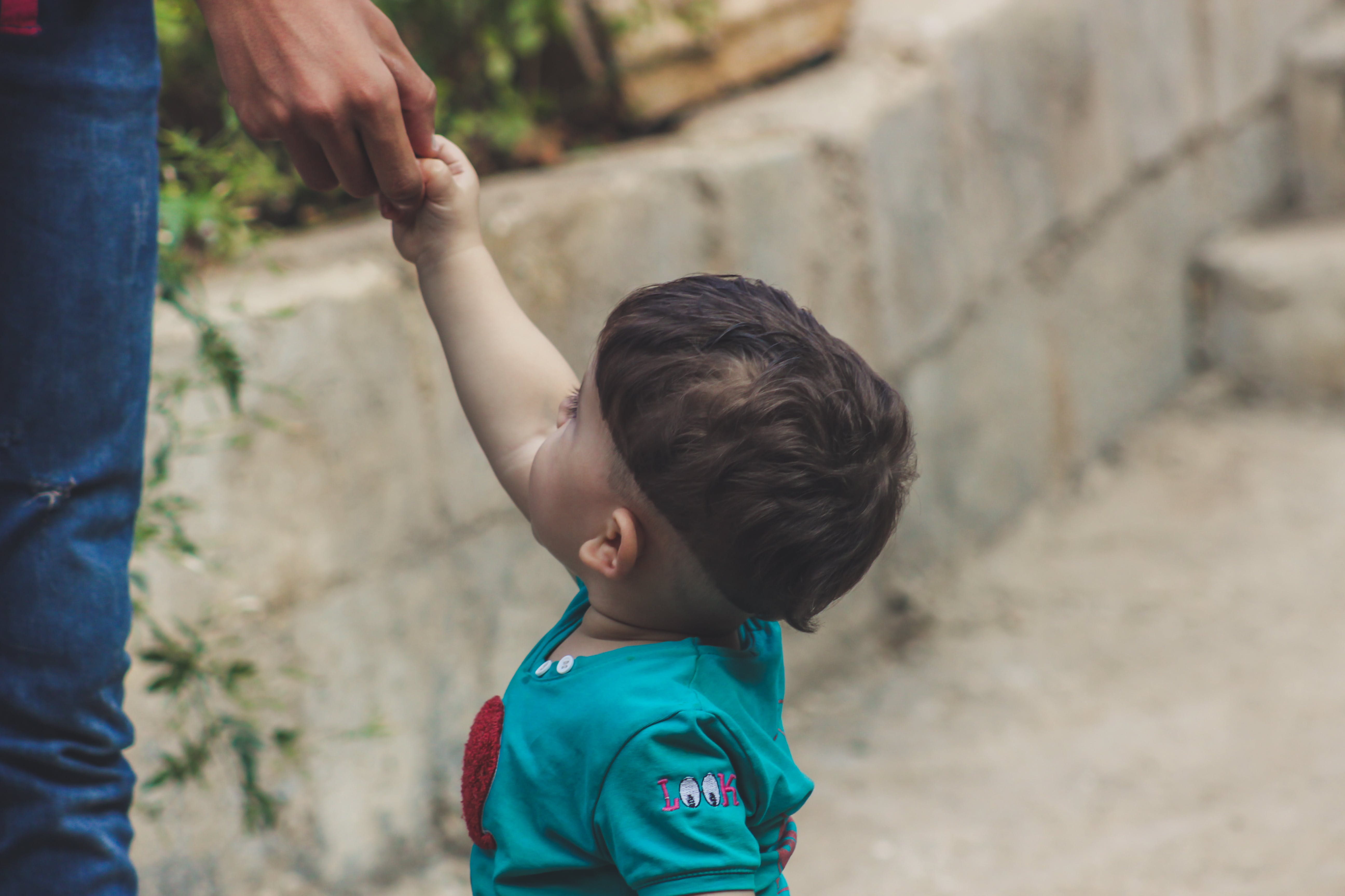 Photography of Baby Holding The Hand of Person