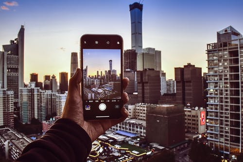 Person Holding Smartphone Taking Photo of High-rise Buildings
