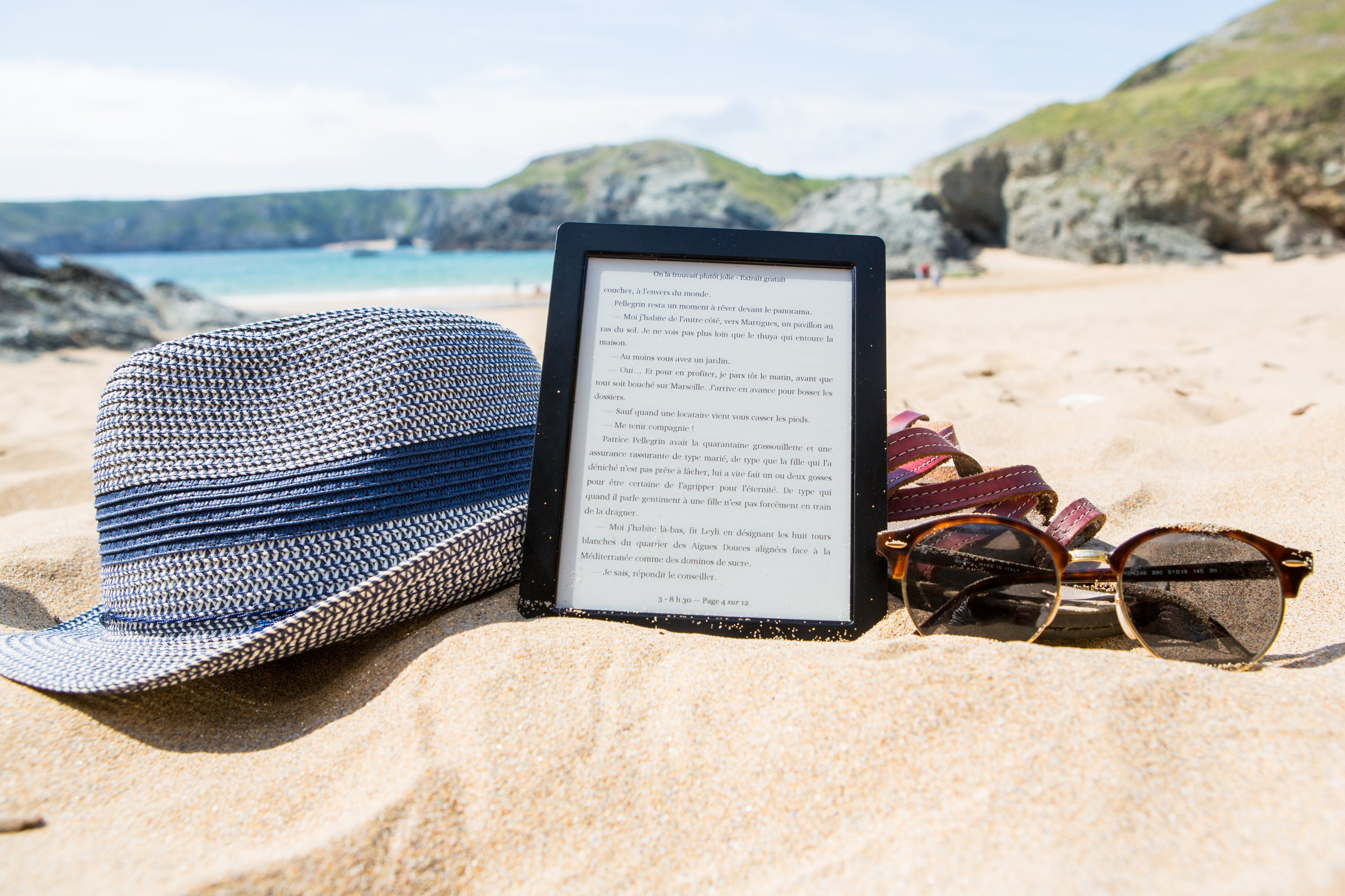 Shallowfocus Photography of Fedora Hat, Photo Frame, and Sunglasses on Beach