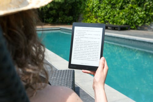 Woman Sitting Beside Pool Holding Tablet