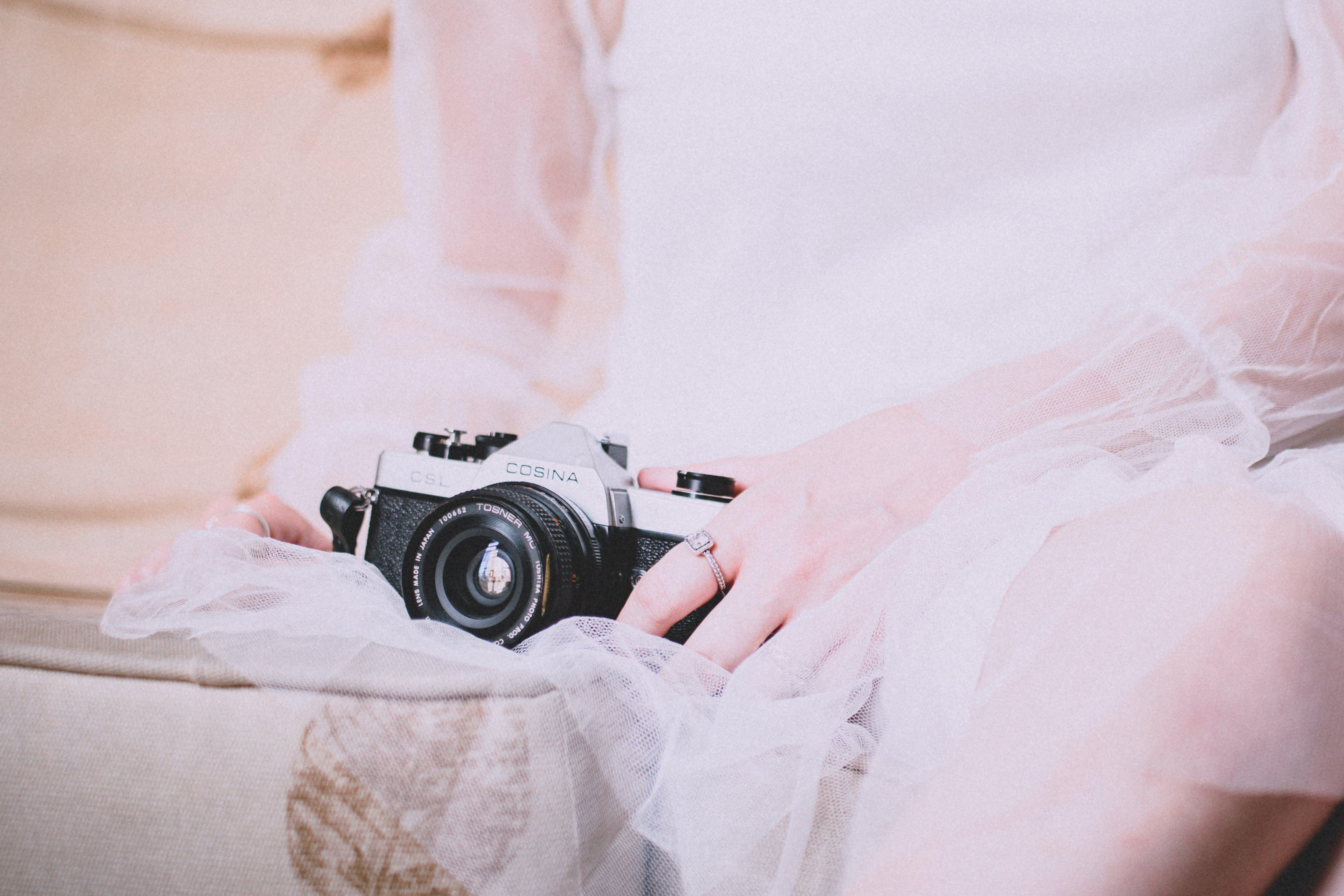 Person Holding Black Mirrorless Camera