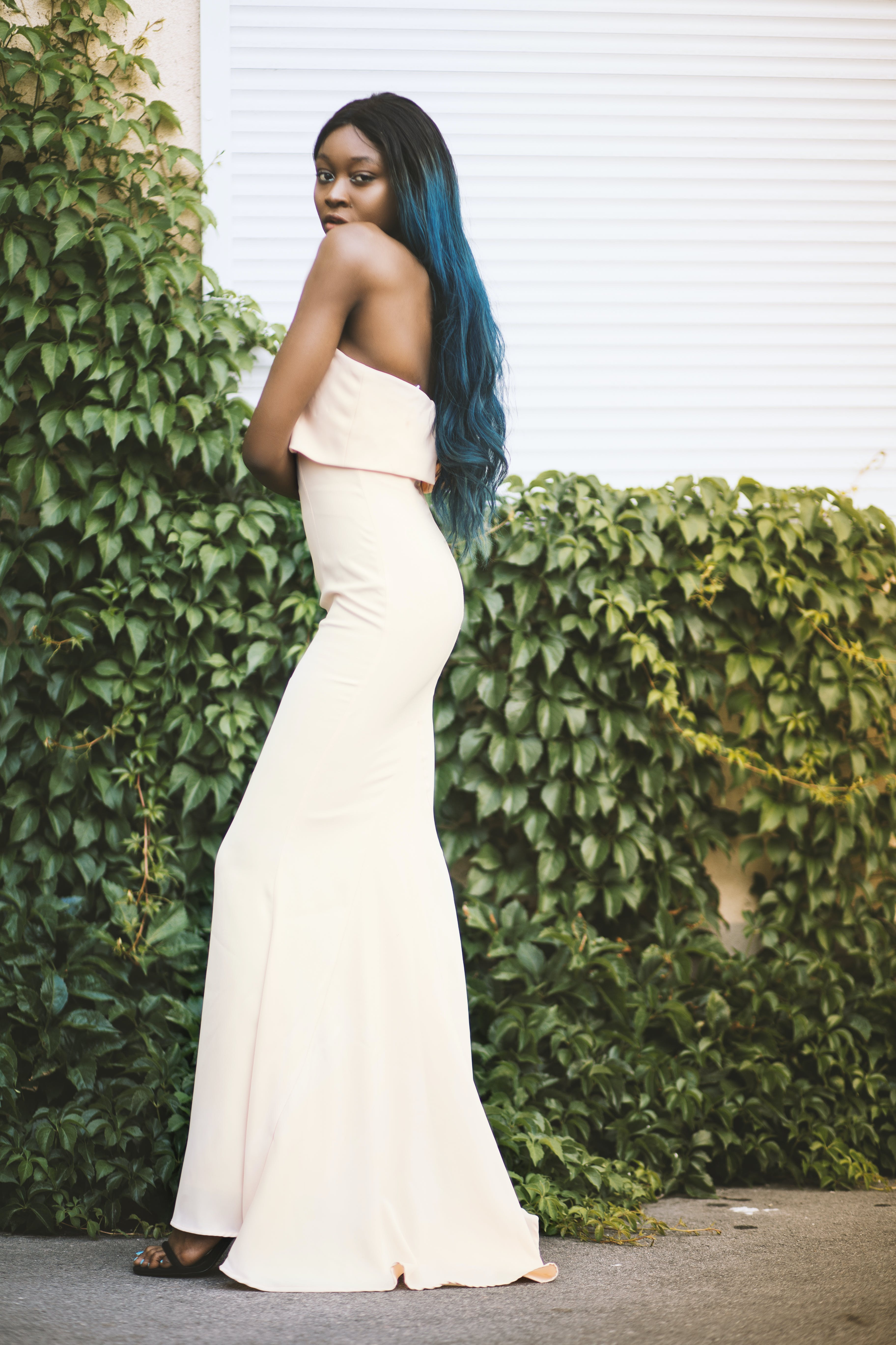 Woman Wearing White Strapless Long Dress Standing Beside Green Plants Hanged on Wall