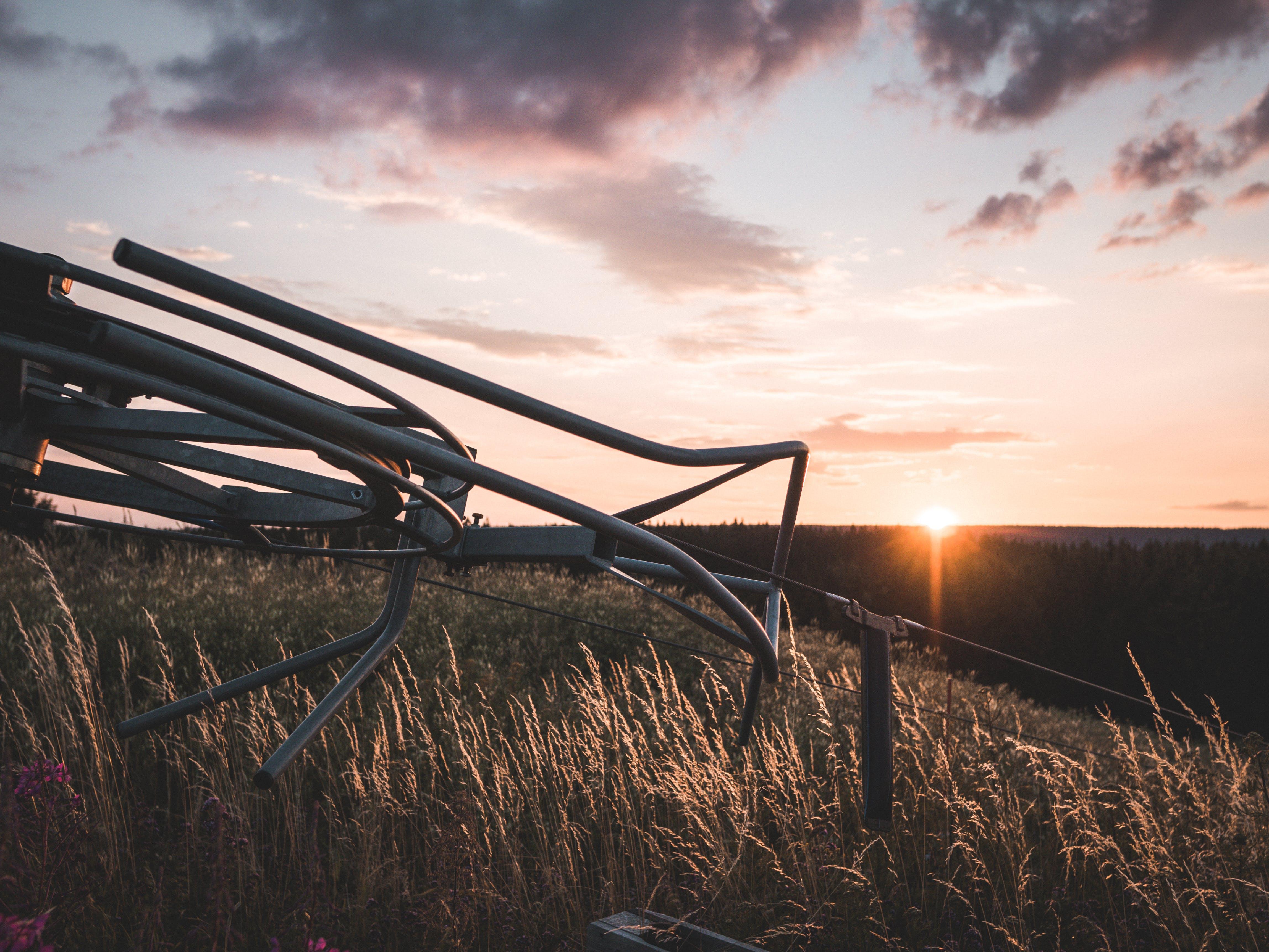 Grey Steel Farm Machine on Field during Orange Sunset