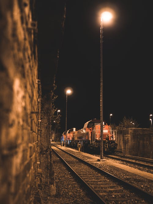 Selective Focus Photo of Red Train on Tracks during Nighttime