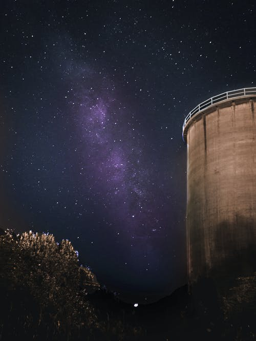 Low-angle Photo of Gray Concrete Building Under Starry Night