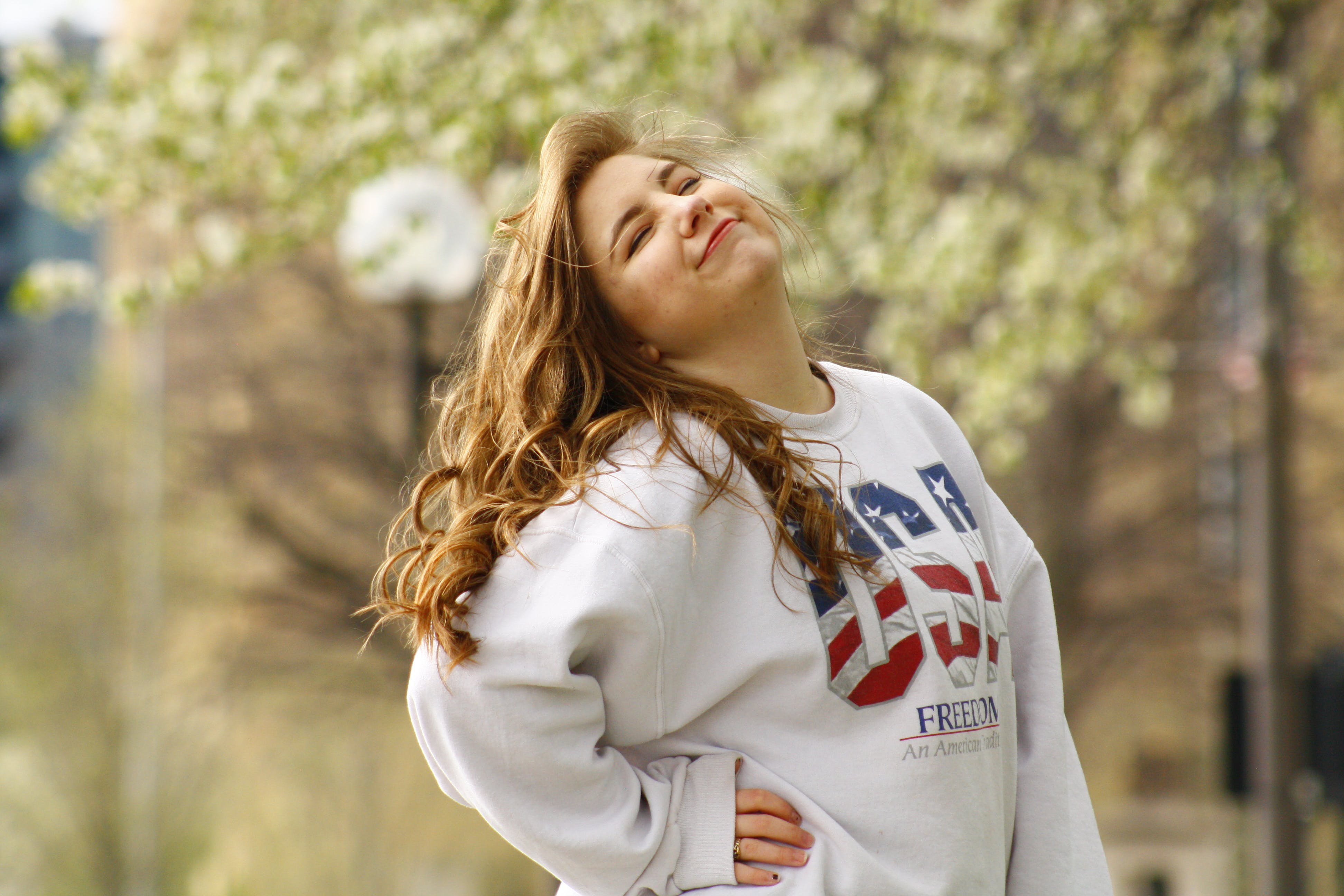 Selective Focus Photography of Posing Woman Wearing White Usa Crew-neck Long-sleeved Shirt