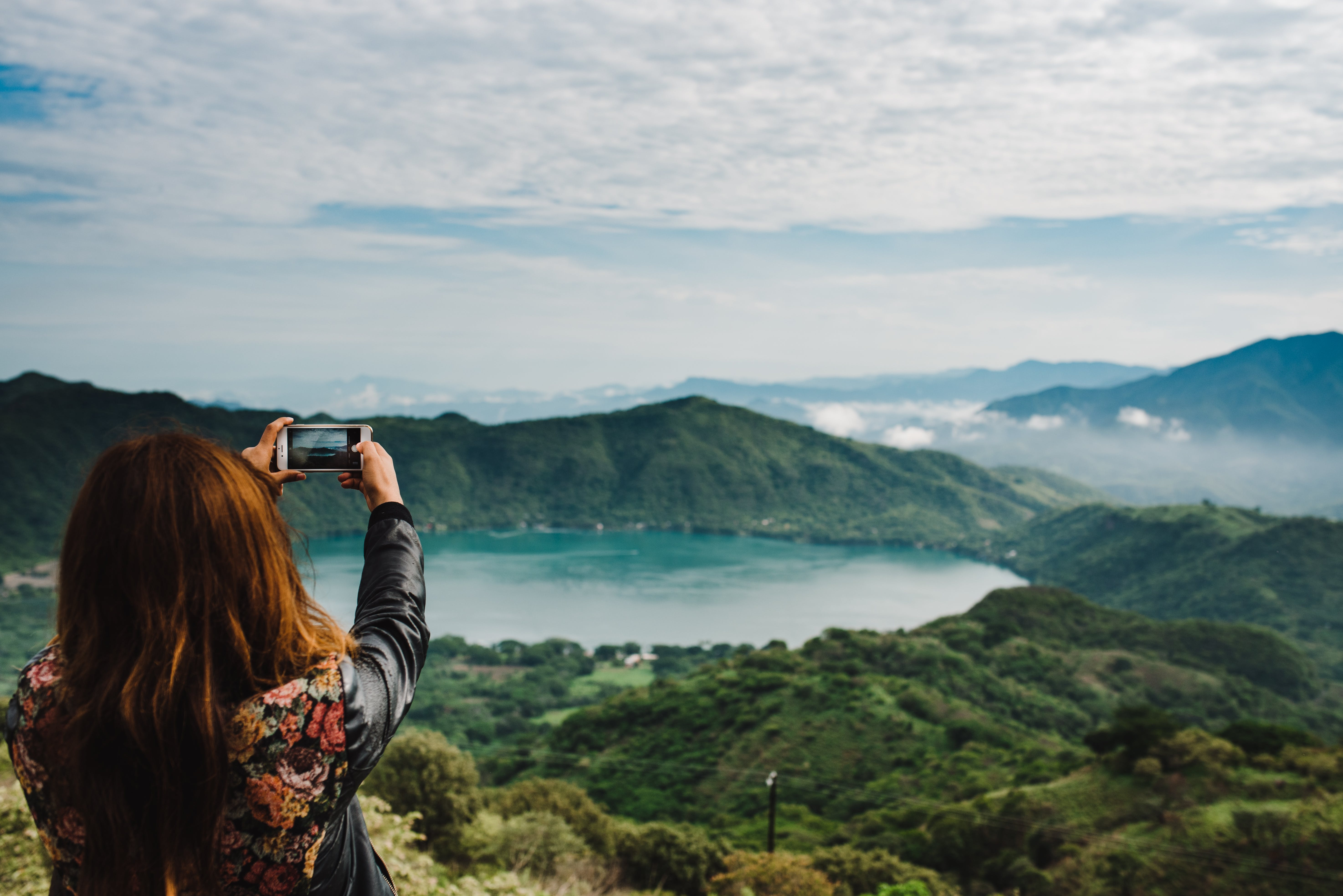 Woman Taking Photo of Green-covered Mountain