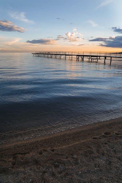 Silhouette of Boardwalk Under Cloudy Skies Shot from Beach