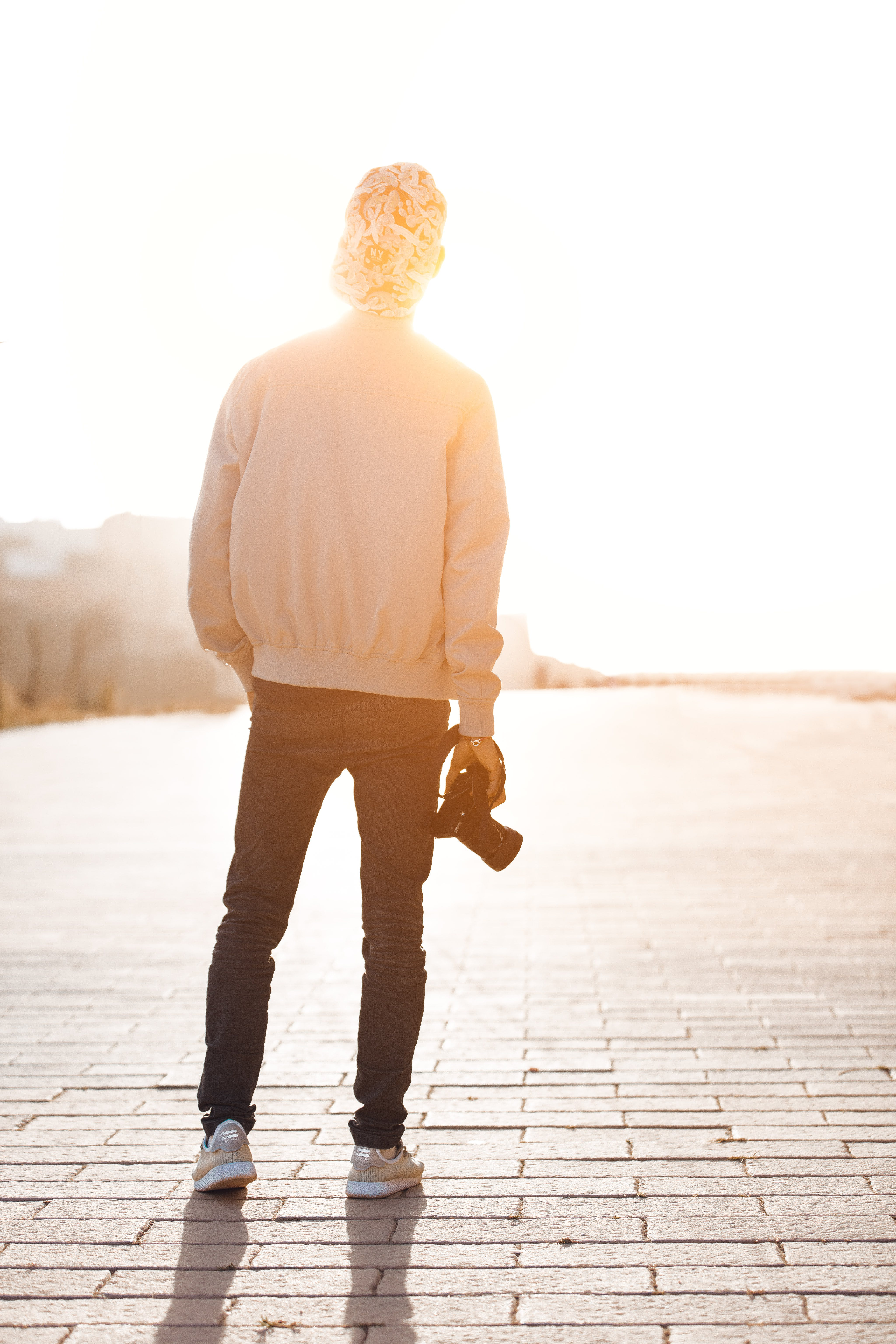Boy Standing While Holding Camera Overlooking Sunlight at Daytime