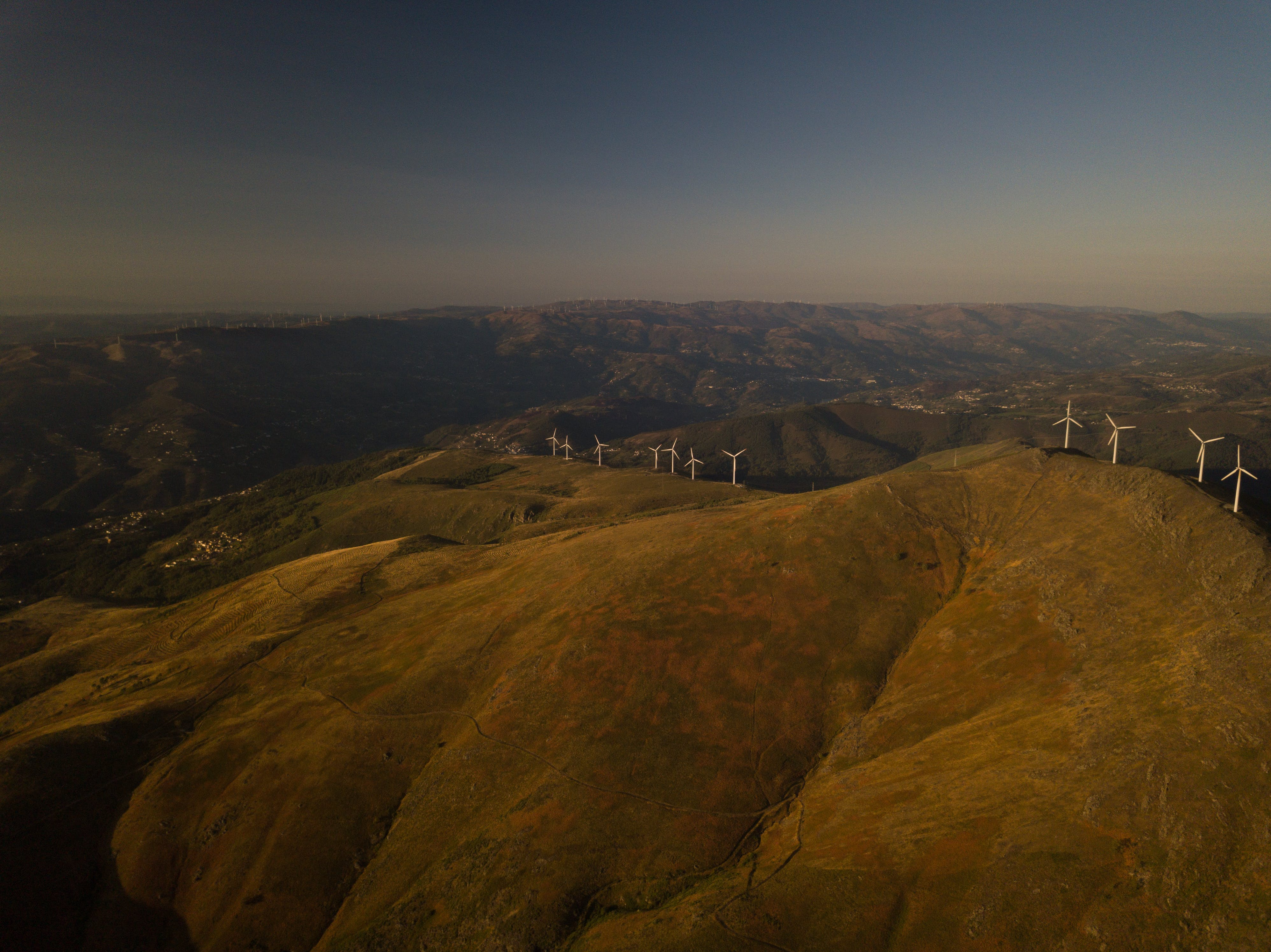 Aerial View of White Turbines on Green Grass Hills