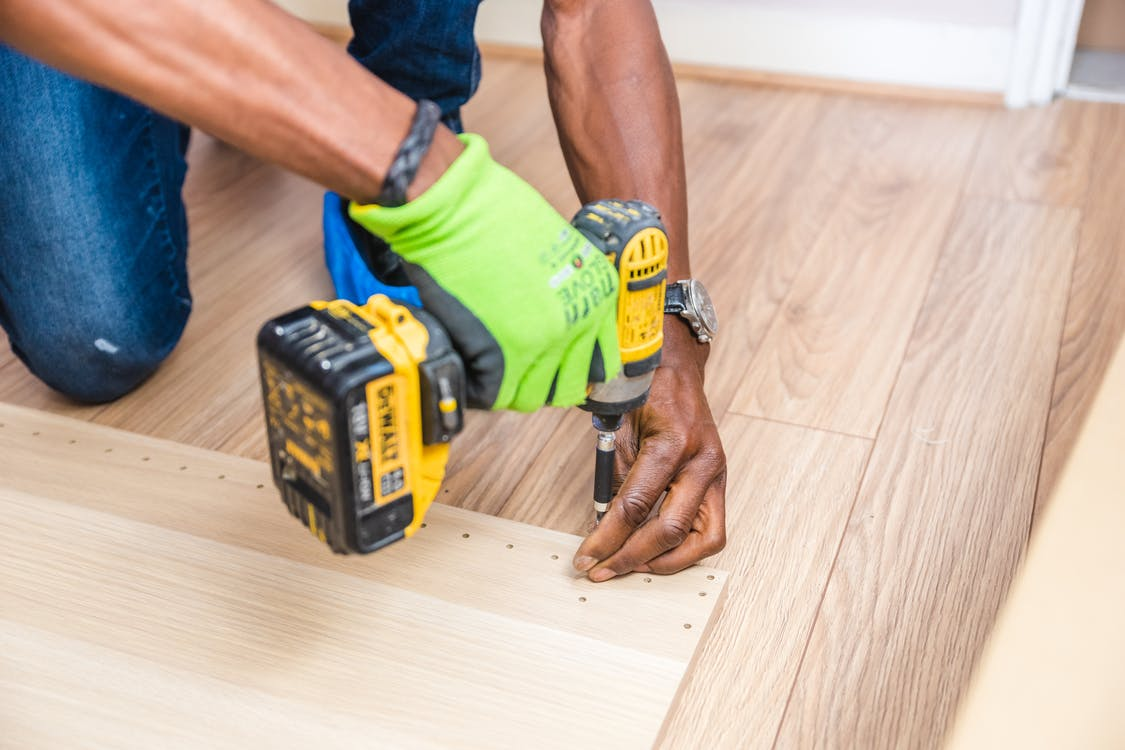 View of a person's hands wearing a single glove and operating a cordless drill while installing a new hardwood floor.