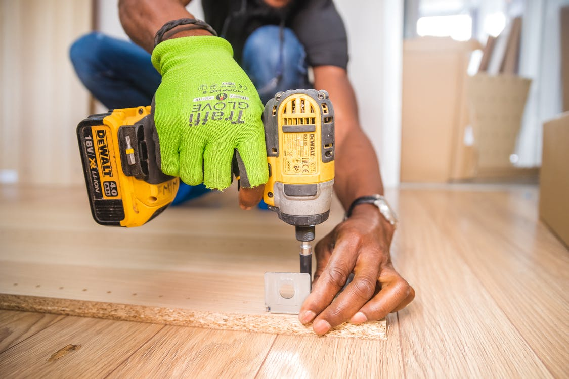 Choosing a contractor who will using Dewalt Cordless Impact Driver on Brown Board