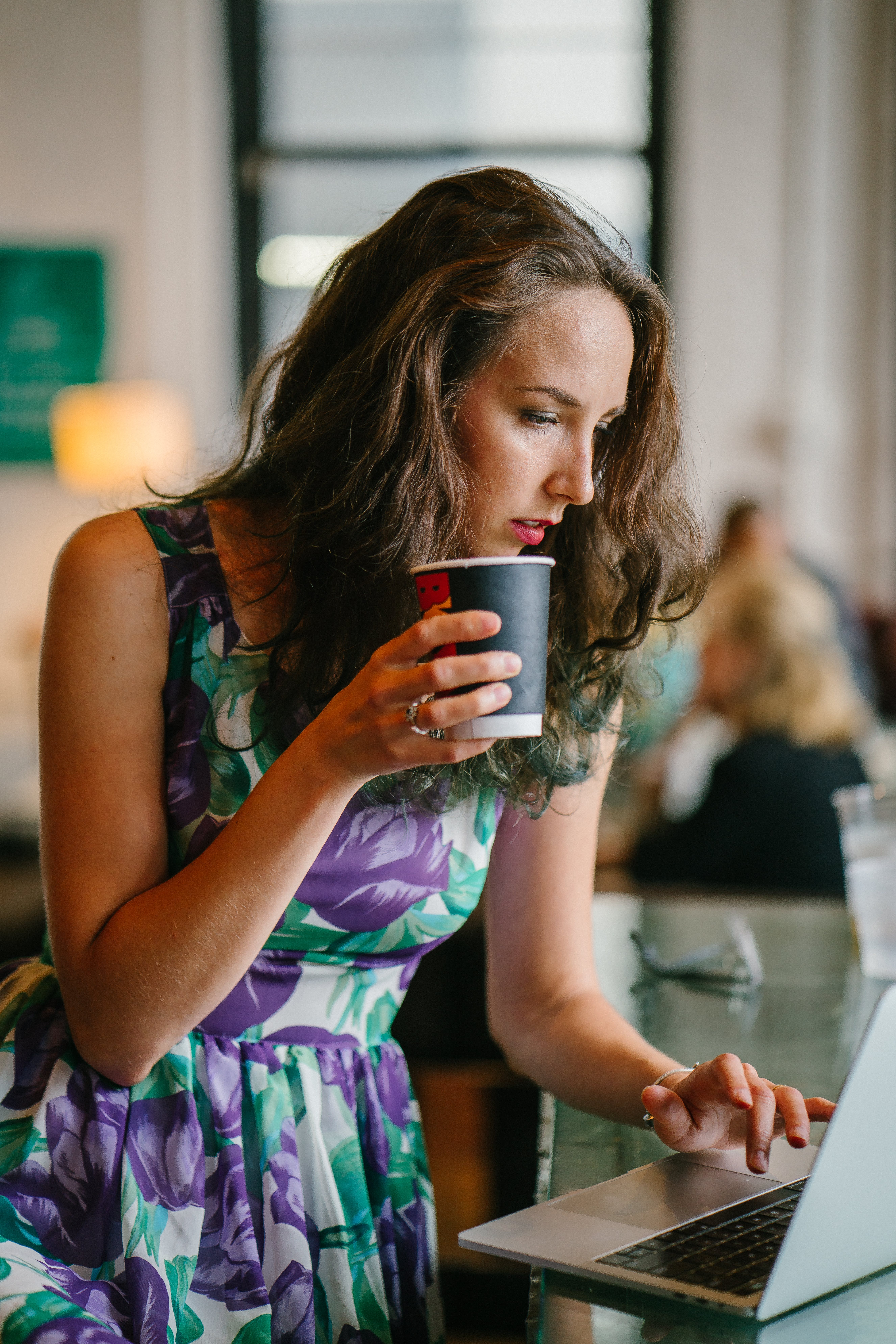 Selective Focus Photography of Woman Holding Disposable Cup Using Gray Laptop on Table