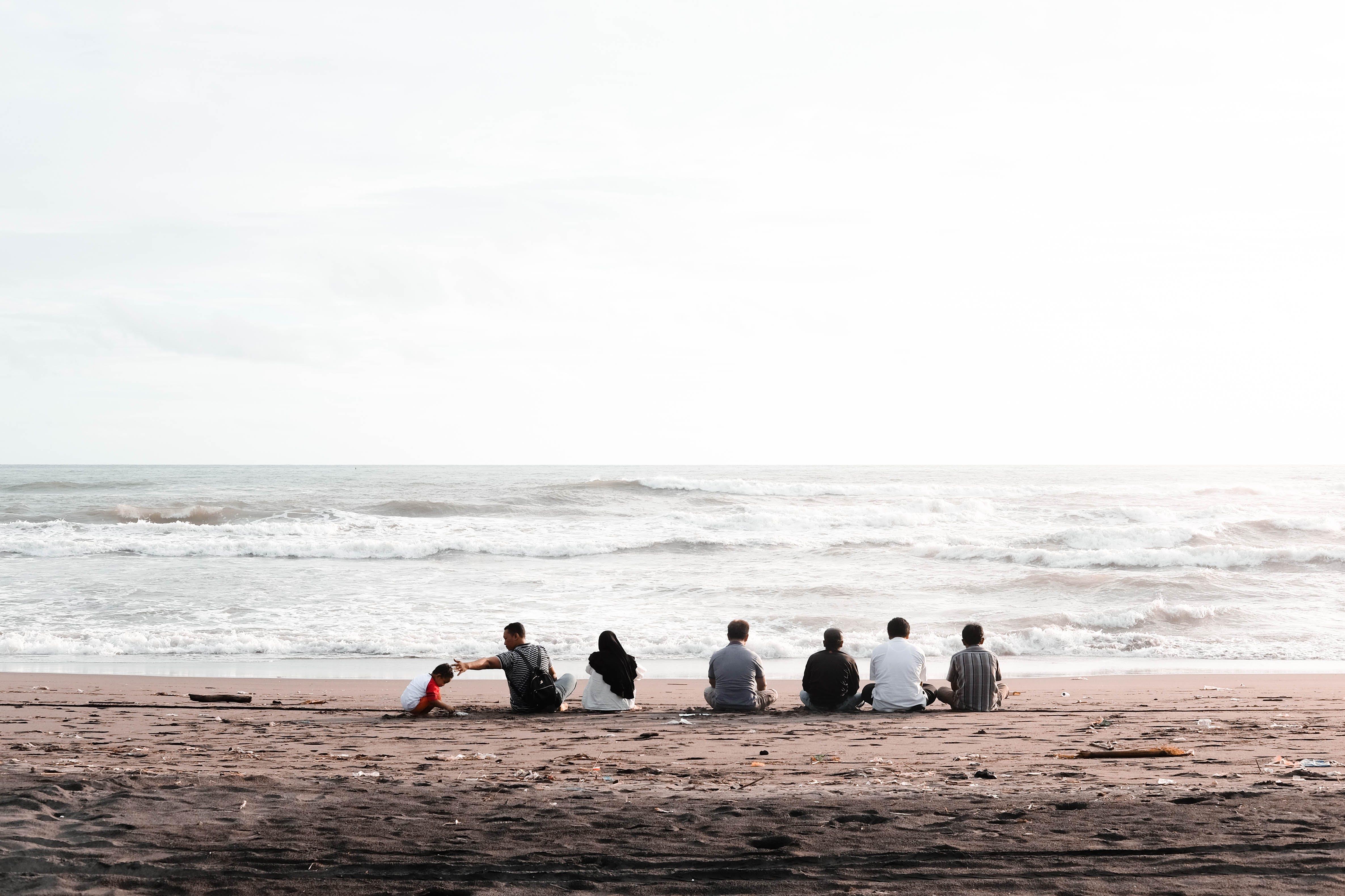 Group of People Sitting on Seashore